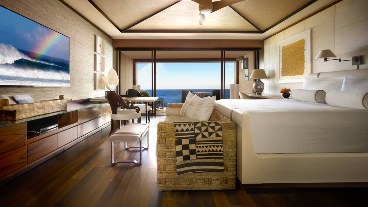 Prime oceanfront room bed with white frame, rattan sofa, long wood dresser, flat-screen tv with rainbow, glass balcony window