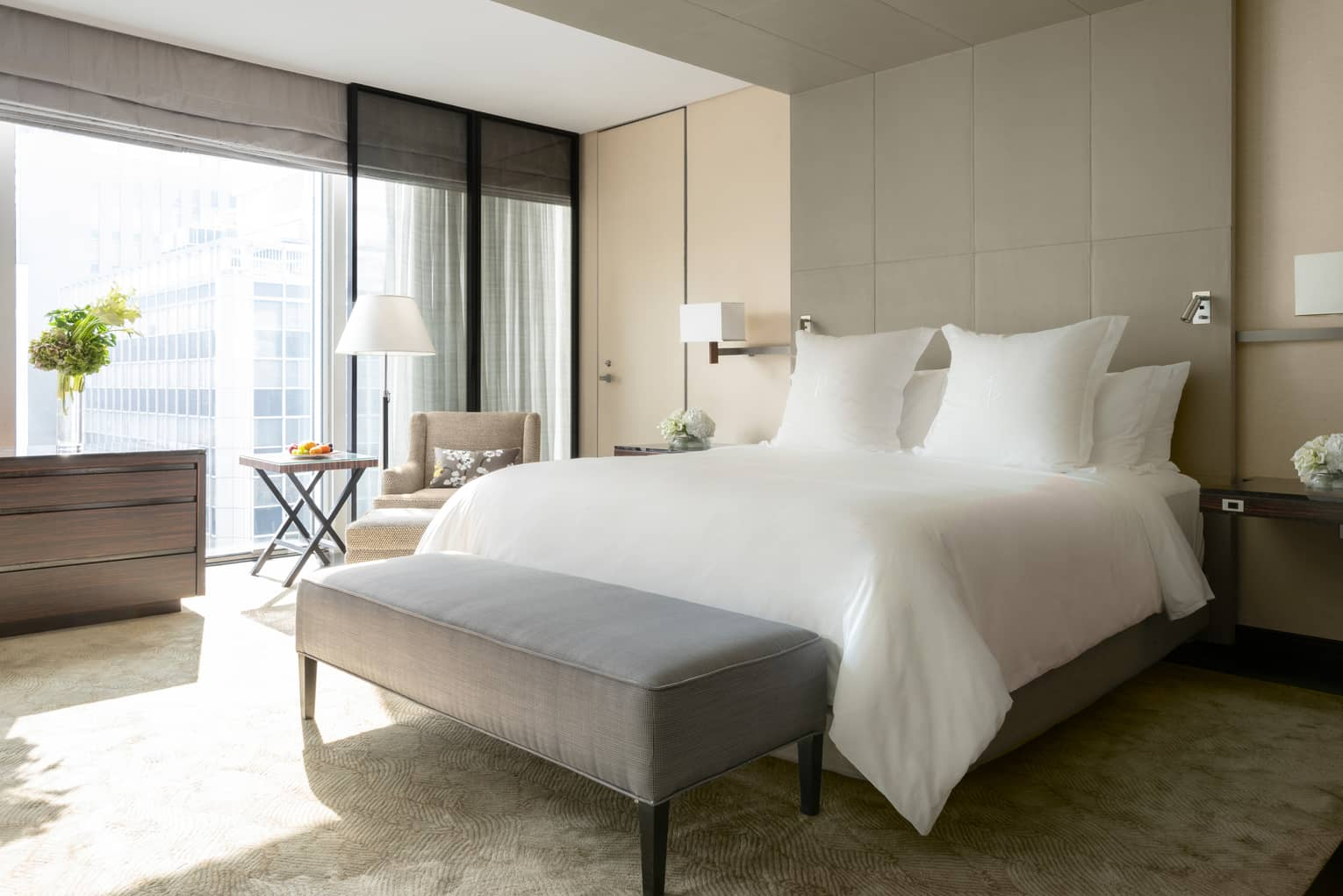 Sunny Deluxe One Bedroom Suite hotel bed with white linens, grey bench at foot
