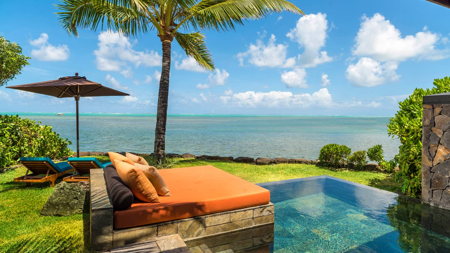 Villa patio, orange lounge bed over stone plunge pool under palm tree, ocean view