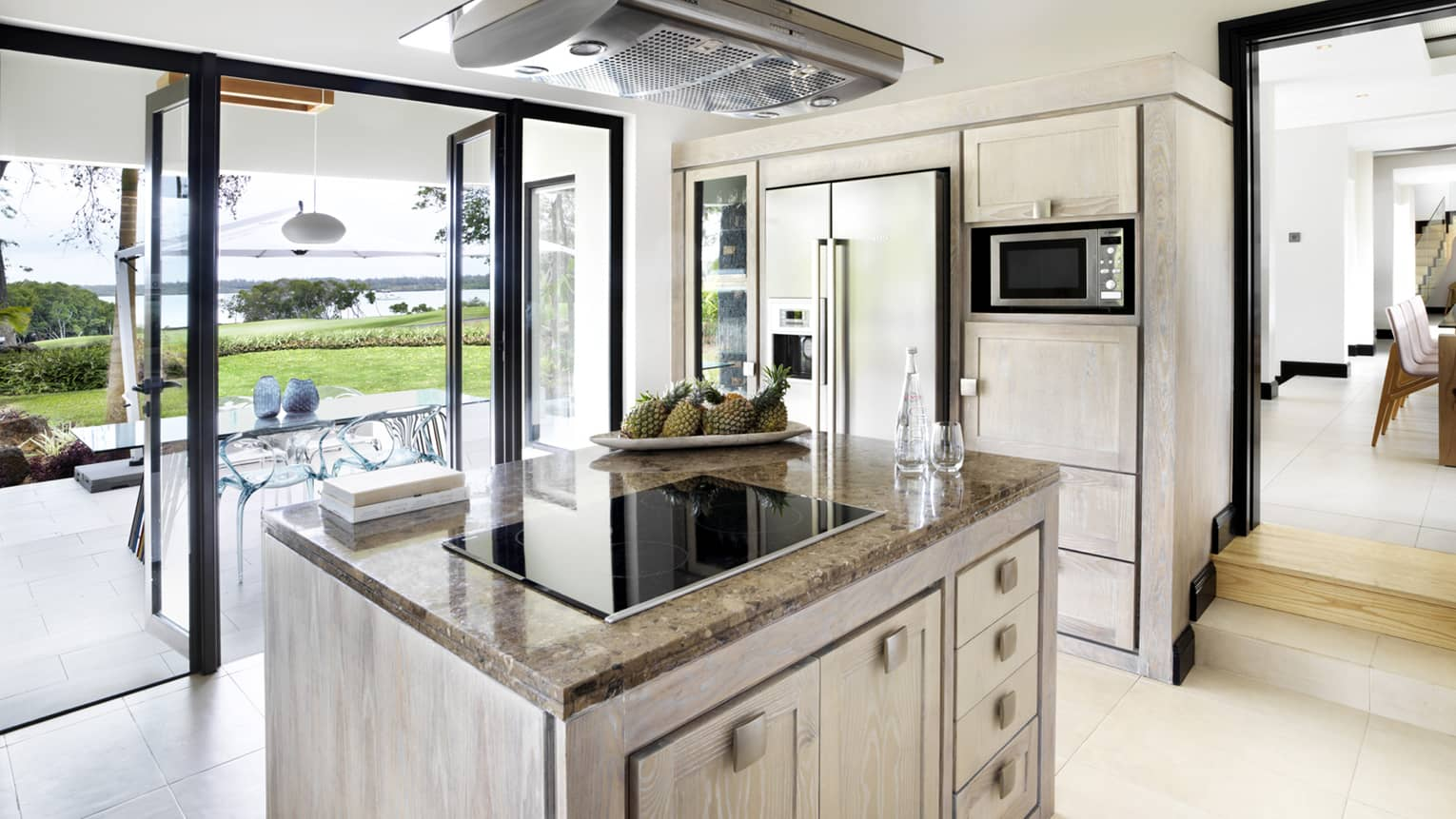 Stove range on marble island in bright, modern kitchen with open glass walls