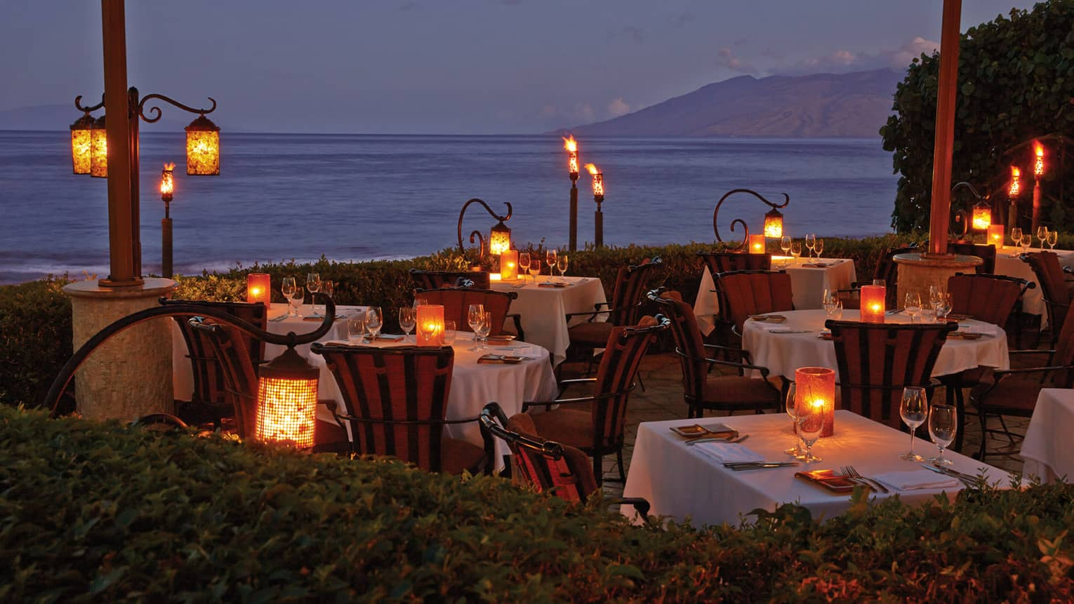 Ferraro restaurant terrace at night with square and round set tables, lit candles, ocean view
