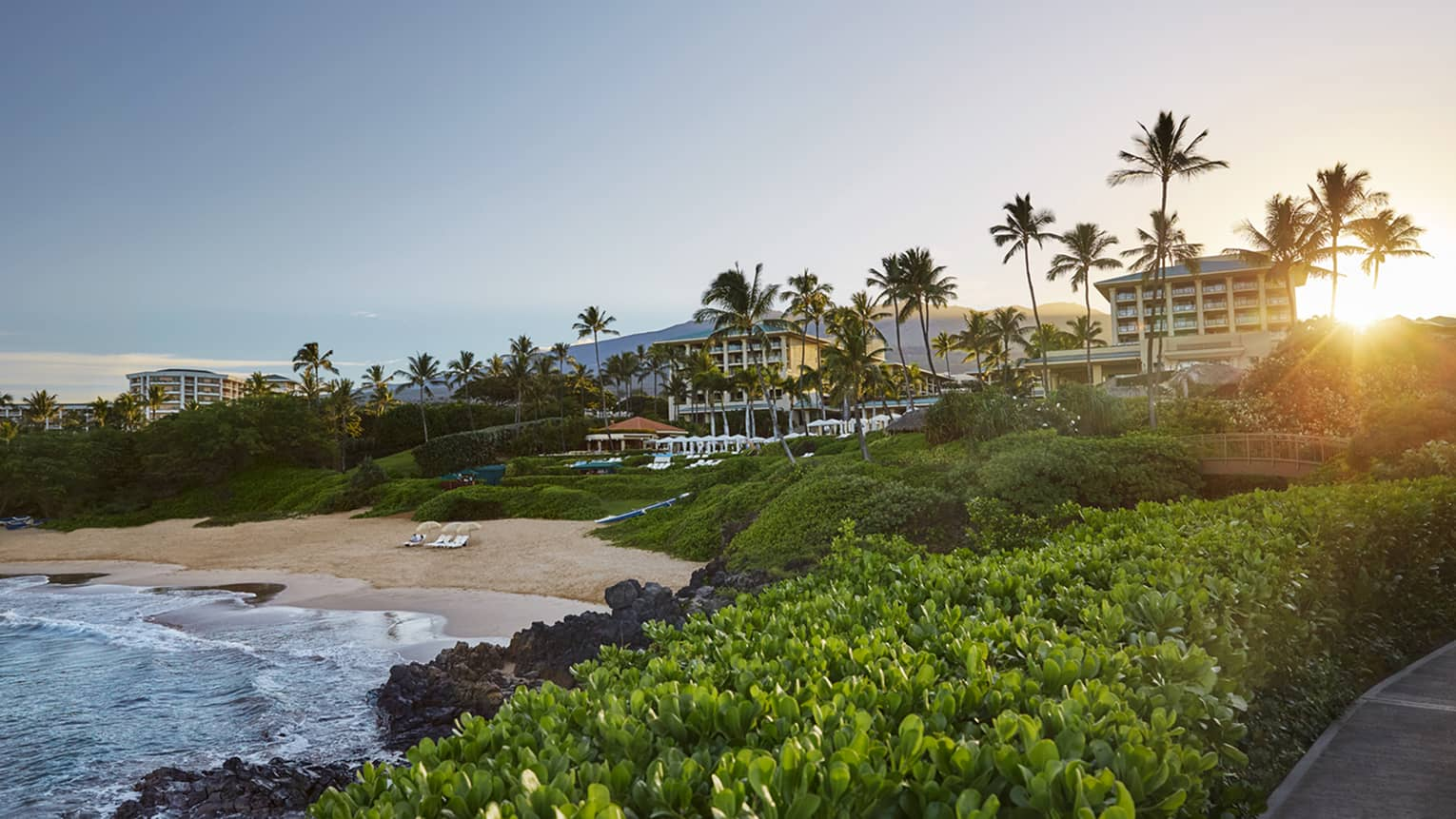 Four Seasons resort and beachfront at sunset, looking over ocean through lush green plants