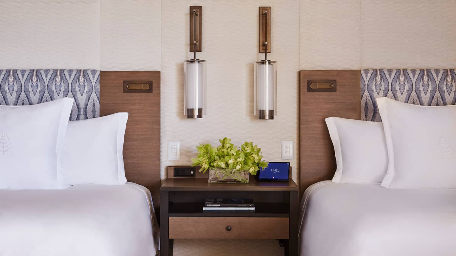 Close-up of two double beds with brown headboards with nightstand and reading lamps in middle