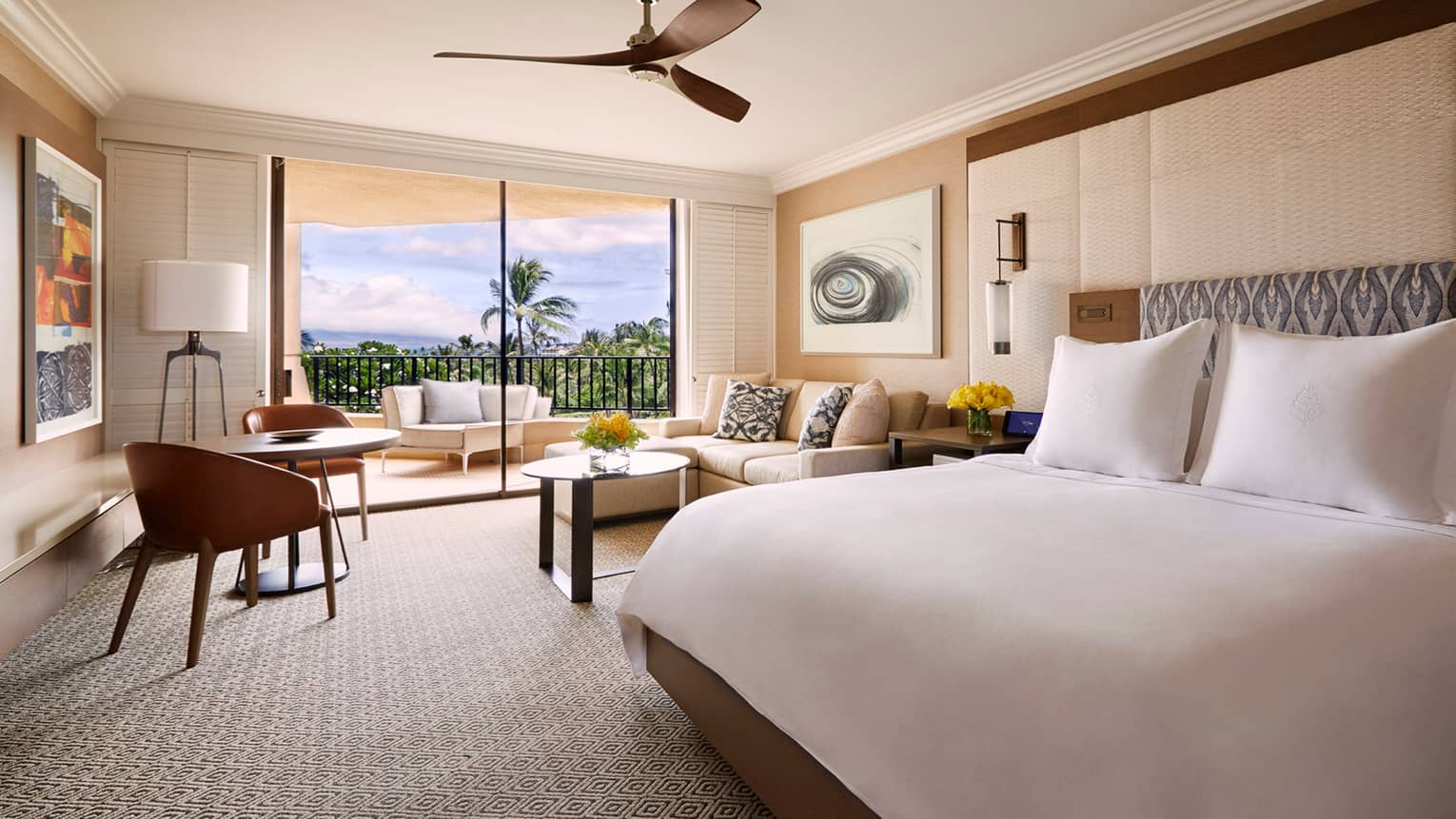Ocean-View Prime room with king-sized bed and two-seat dining table, white sofa beside patio door