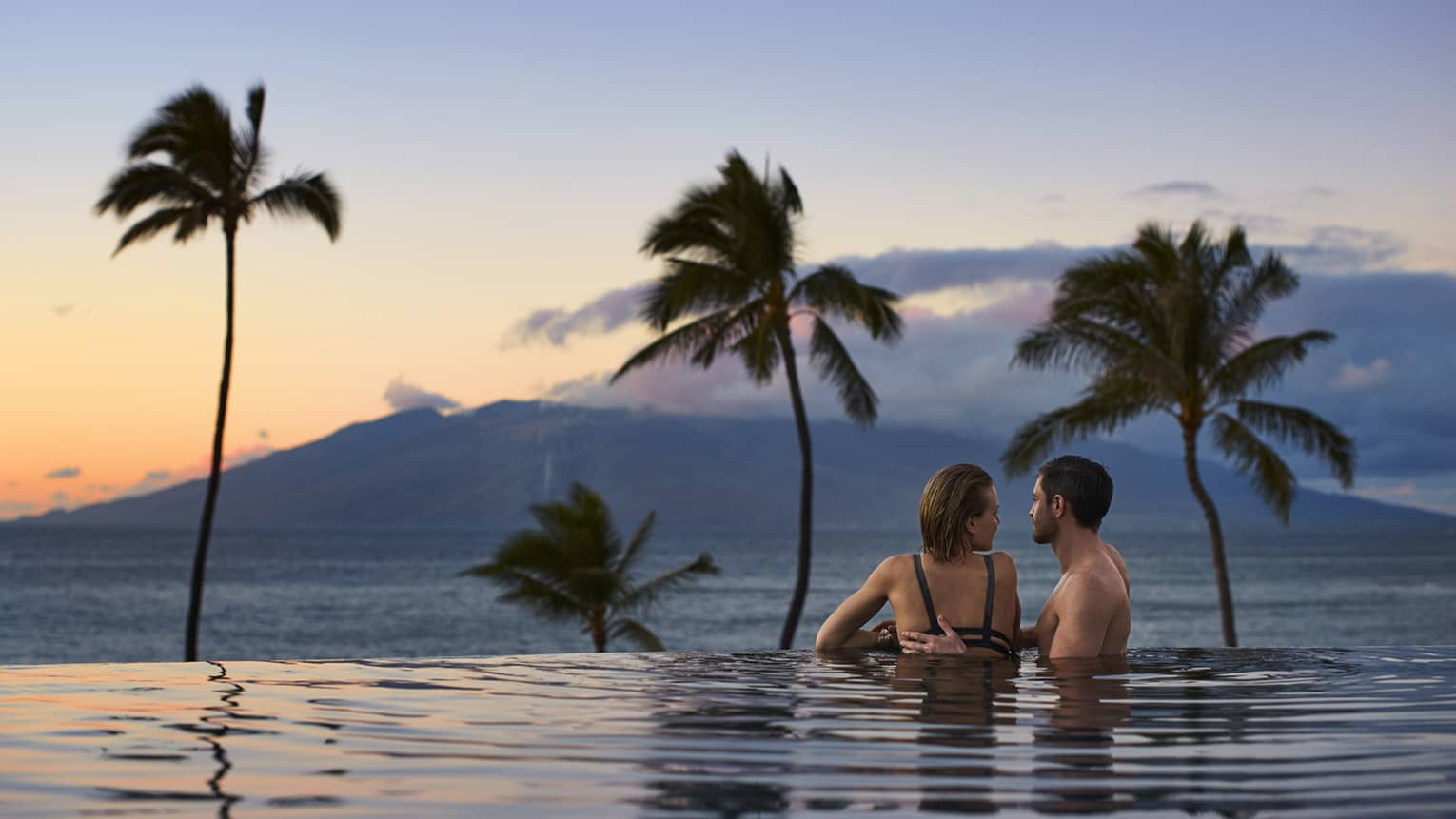 Man rests hand on woman's shoulder in infinity swimming pool, looking out at ocean, mountain and sunset