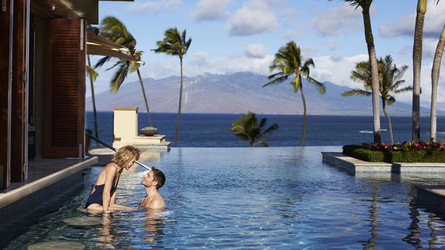 Man and woman at stools of swim-up bar in Serenity Pool, views of Lanai and the West Maui Mountains