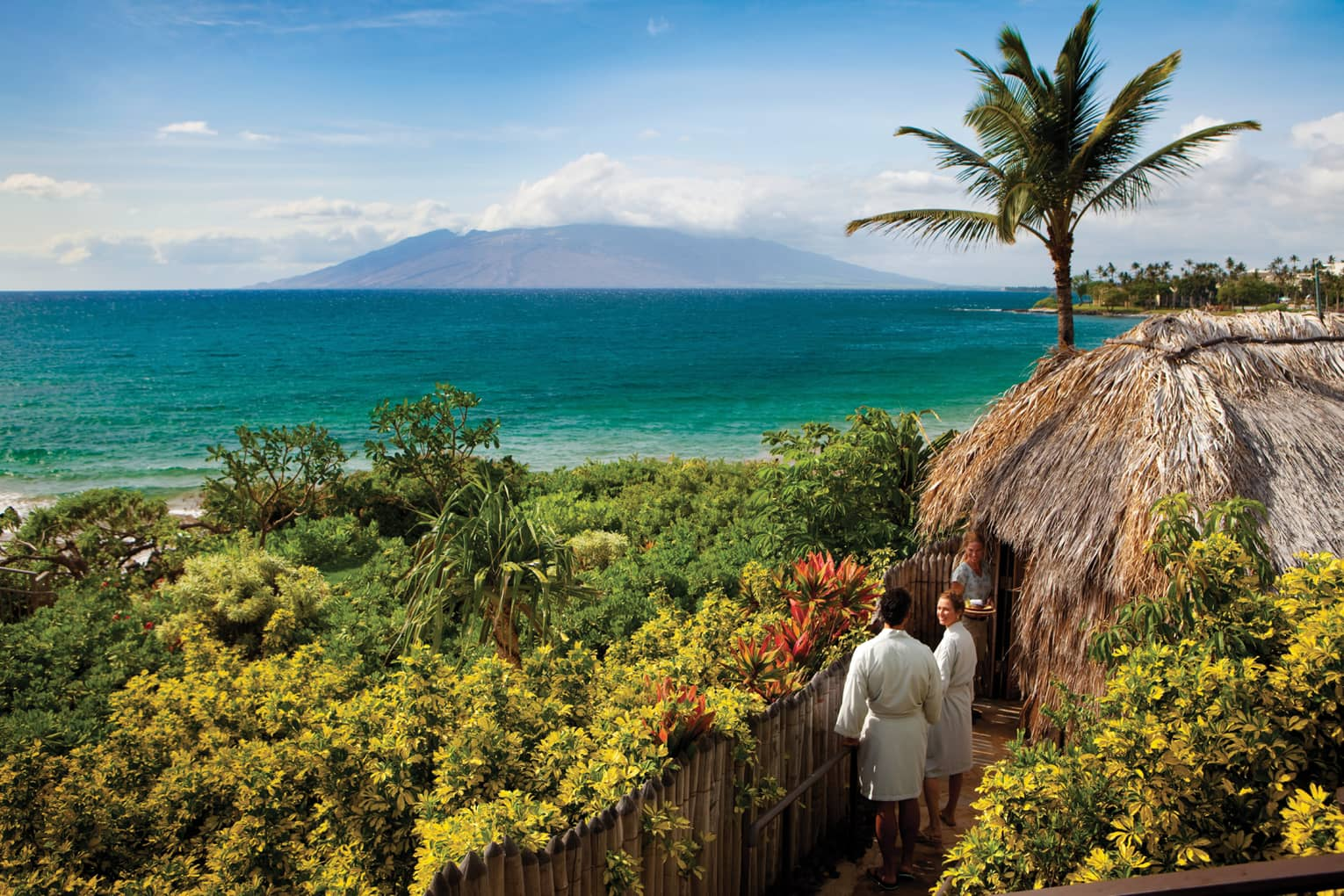 Couple in white bathrobes follow spa attendant into thatched-roof hut on path looking out at ocean
