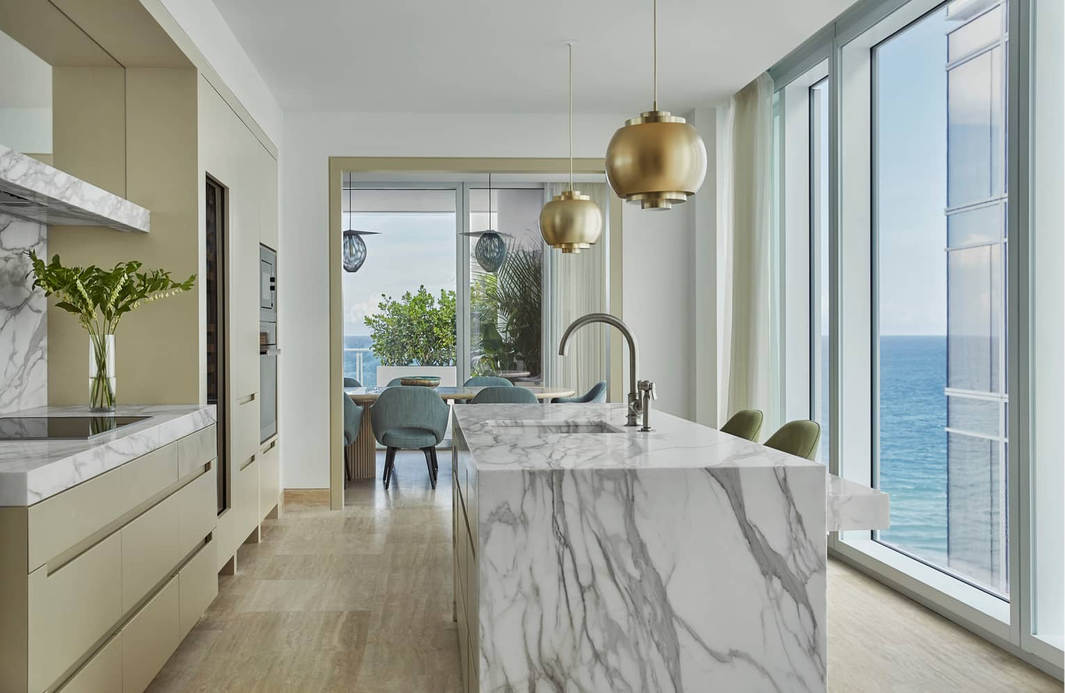 Retro-style brass lamps above grey marble kitchen island, glass wall with ocean views