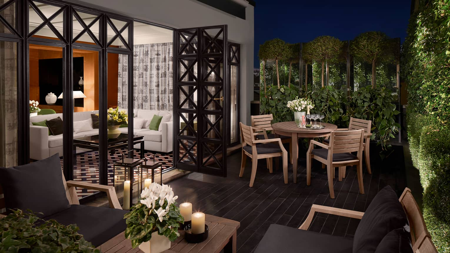 Balcony with wood tables and candles, chairs with black cushions, open doors to suite, white sofa
