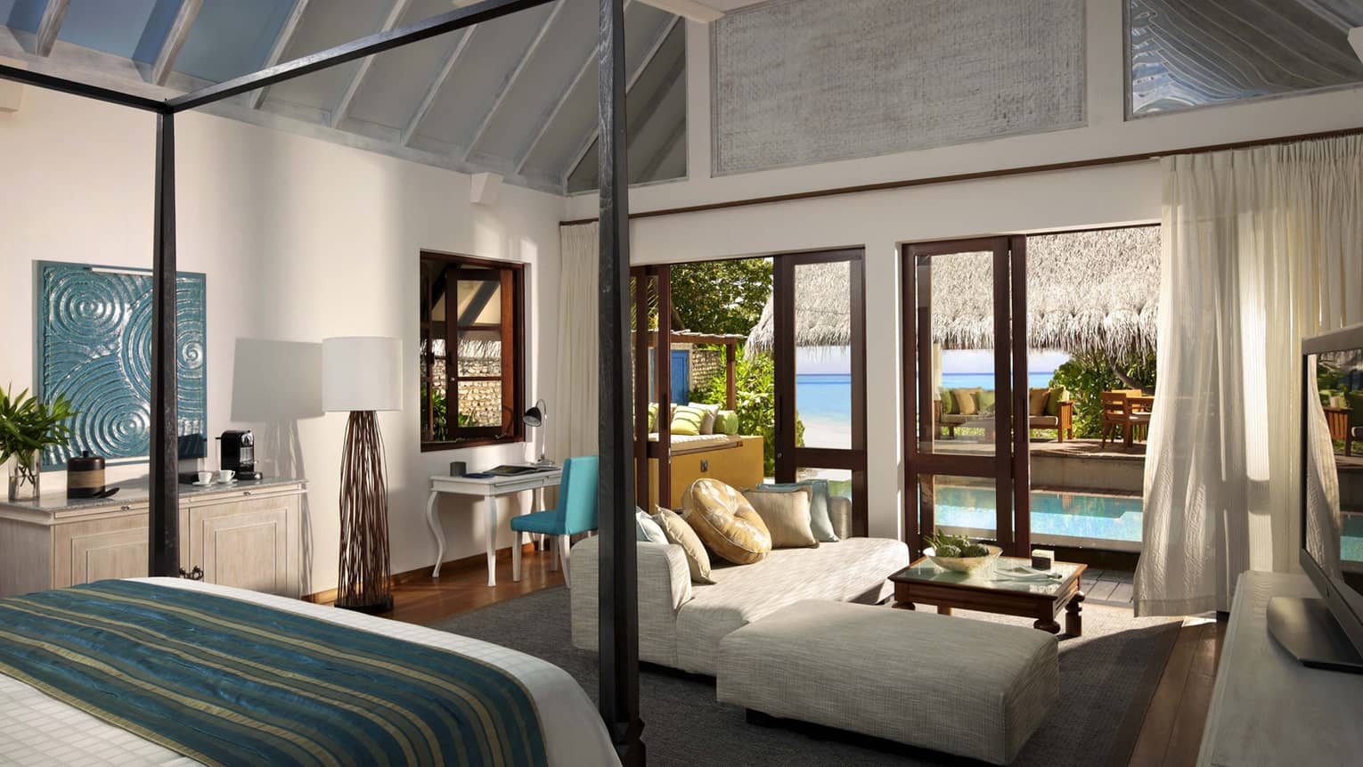Maldives bedroom with lounge area and a look out onto the ocean