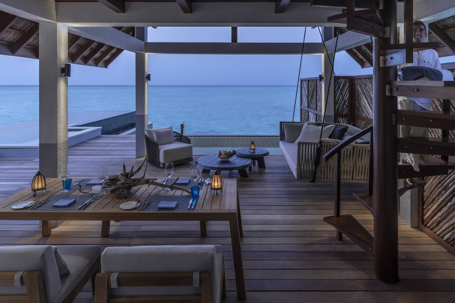 A dining table is arranged near the lounge area of an Over Water Villa with an ocean view