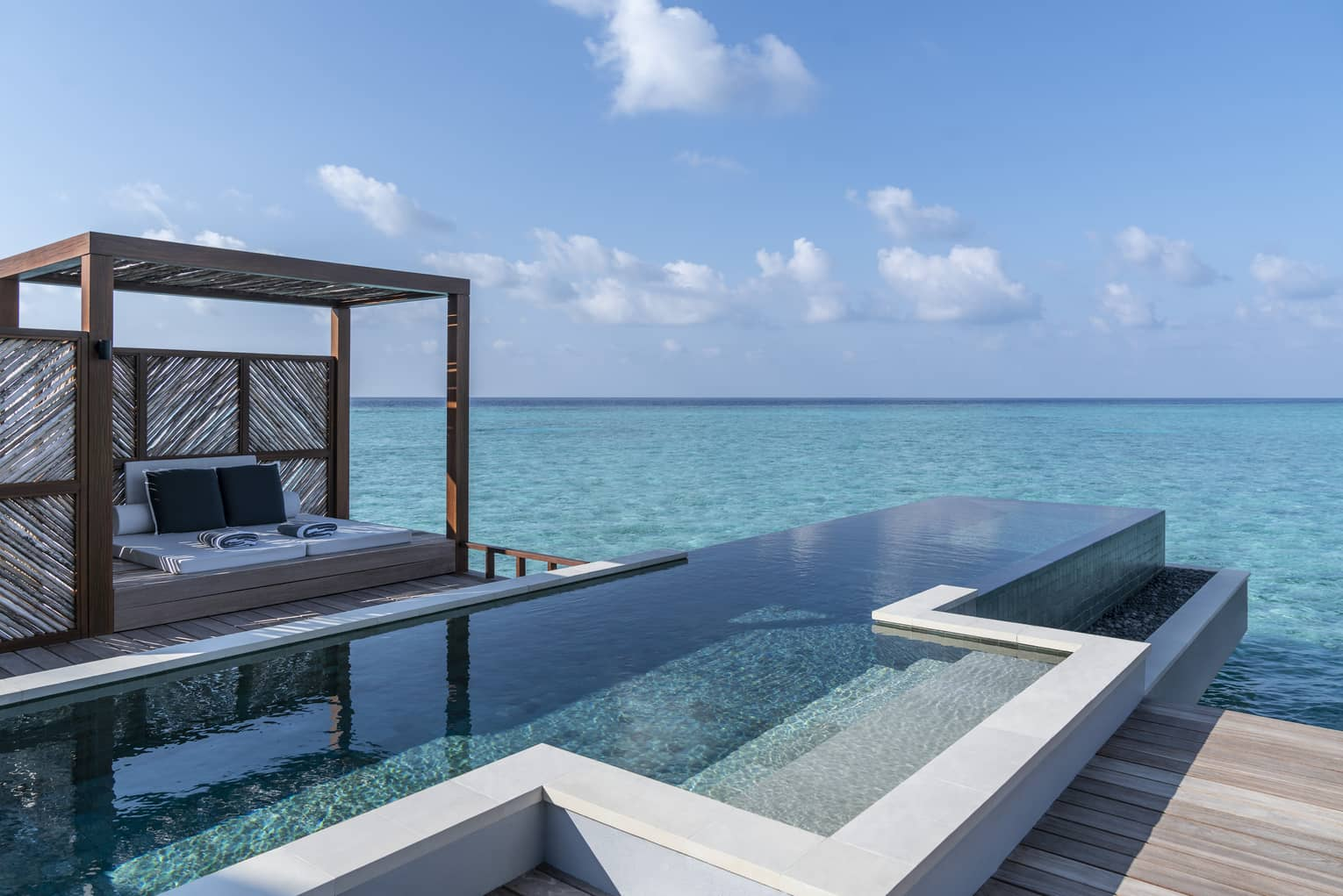 An oceanside infinity pool with a covered cabana