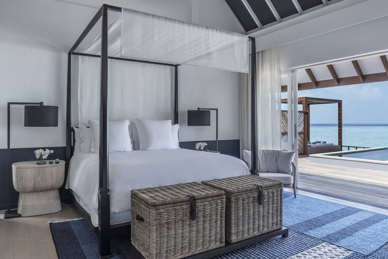 A four poster bed near a sliding door leading to an oceanside pool