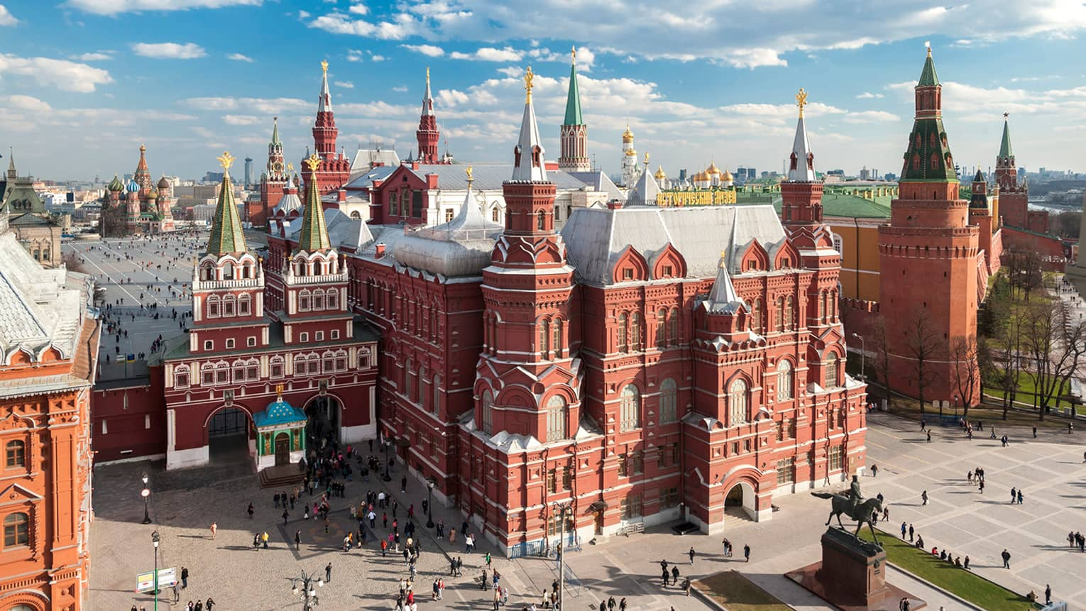People walking in front of the State Historical Museum in Moscow's Red Square on sunny day
