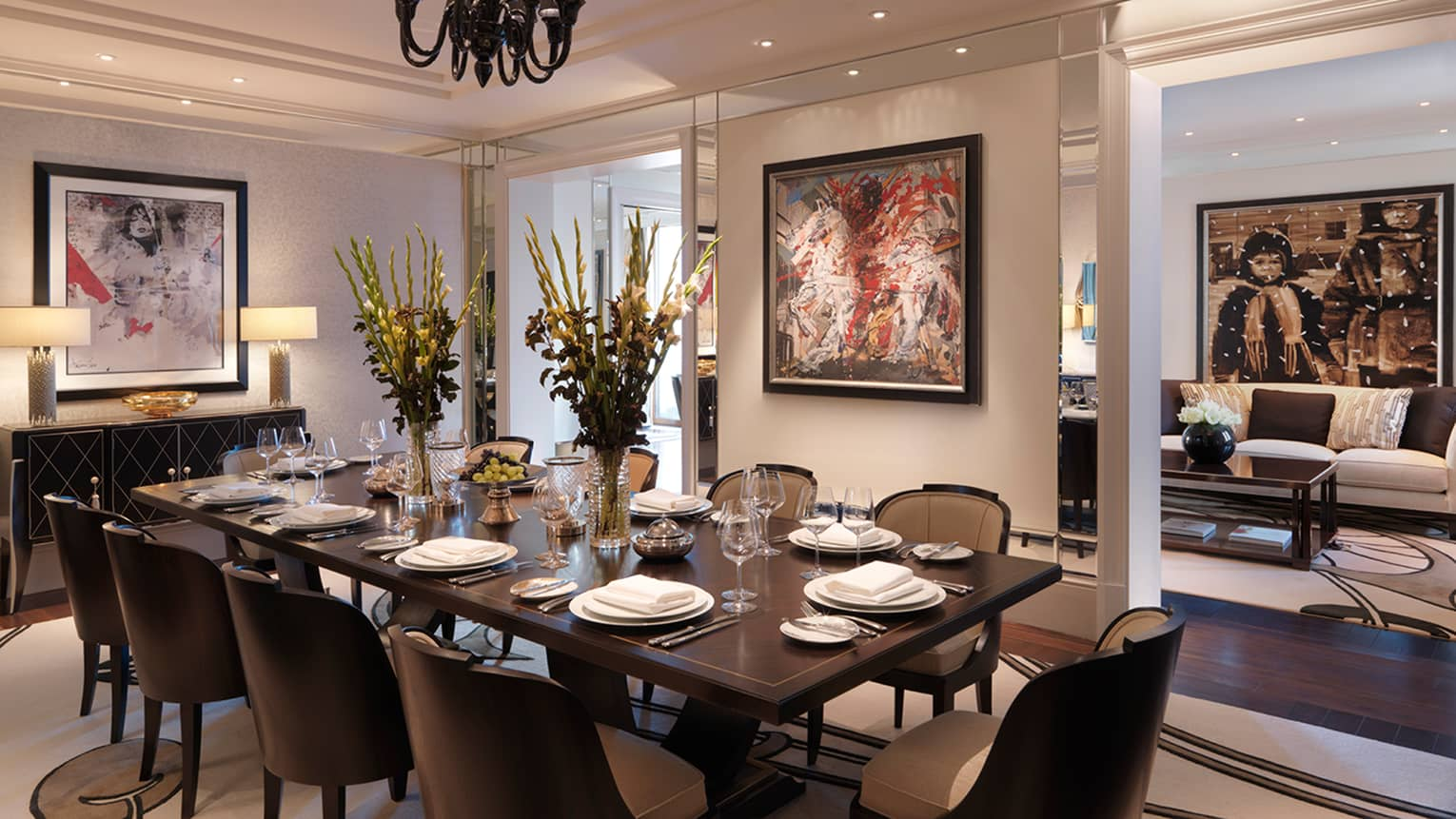 In-room dining table with seating for 10, tall flower bouquets in crystal vases and modern paintings on wall
