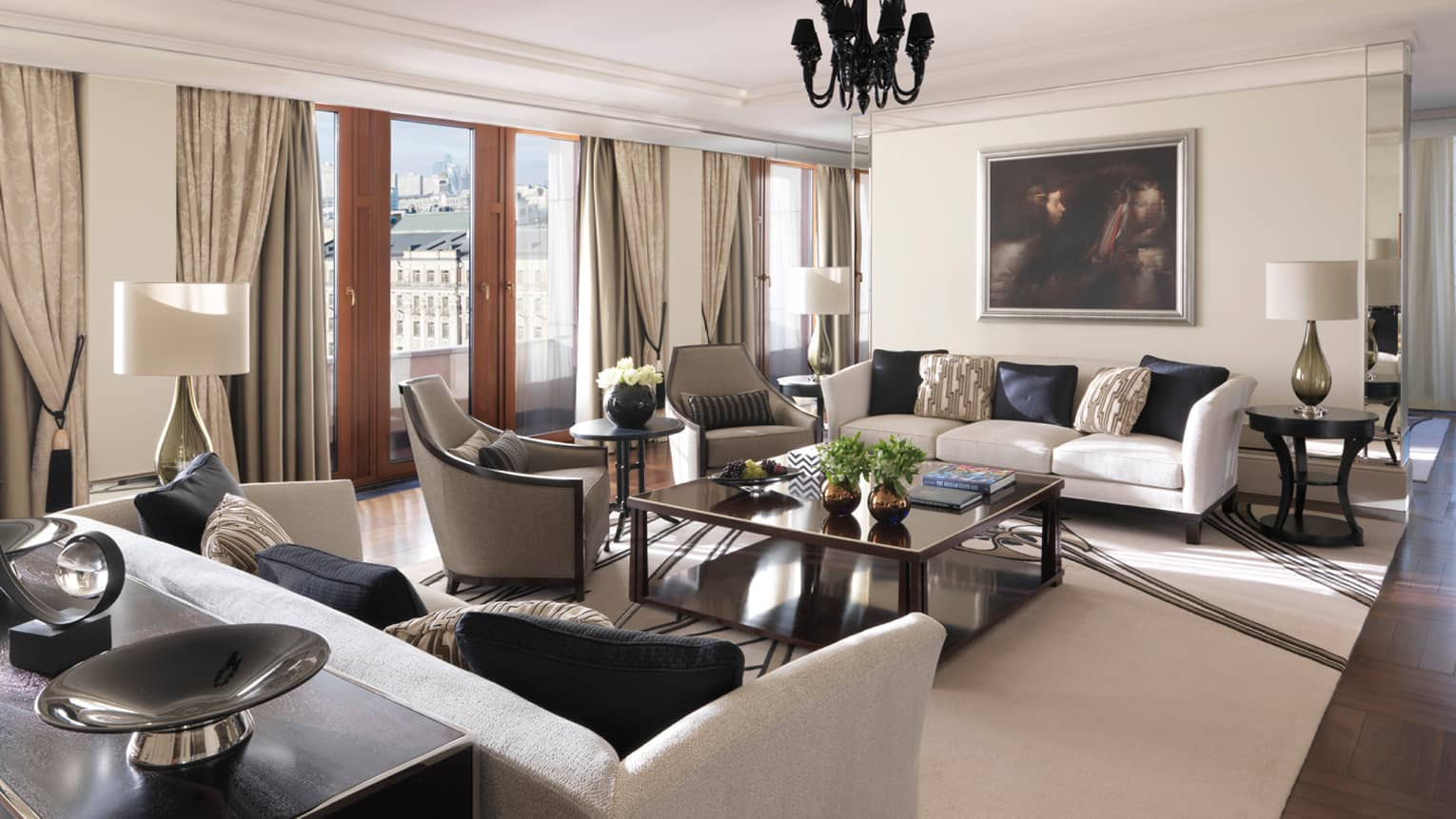 Sunny Minin Presidential Suite living area with white sofas, grey chairs, brass coffee table and vase