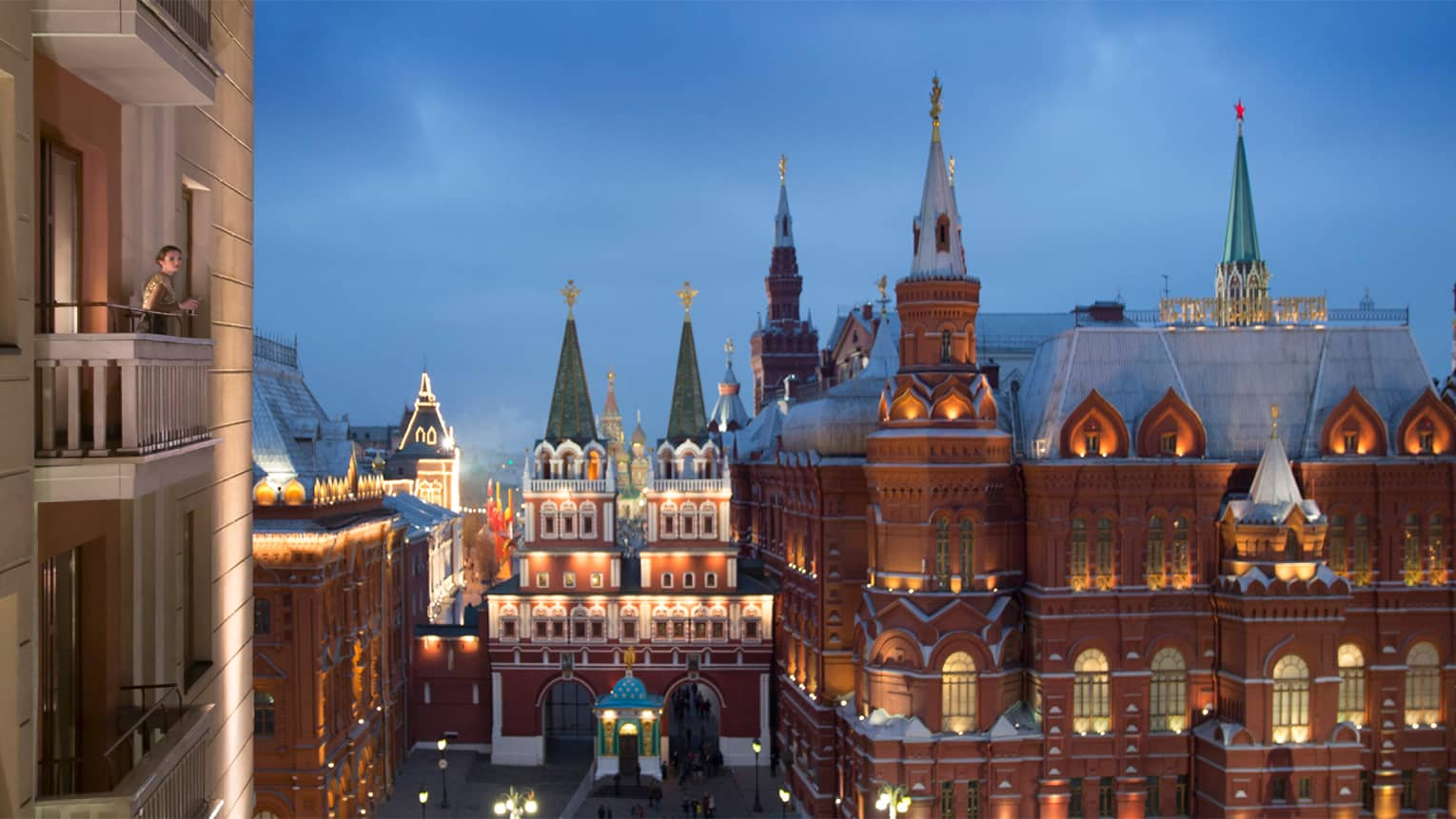 Woman stands on hotel balcony at night, looks out at Red Square historic buildings and lights