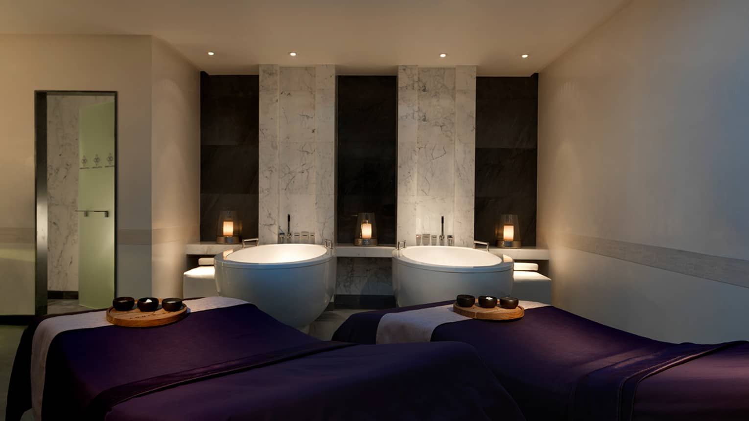 Couples Suite spa room with massage tables, sinks side-by-side in candle-lit room