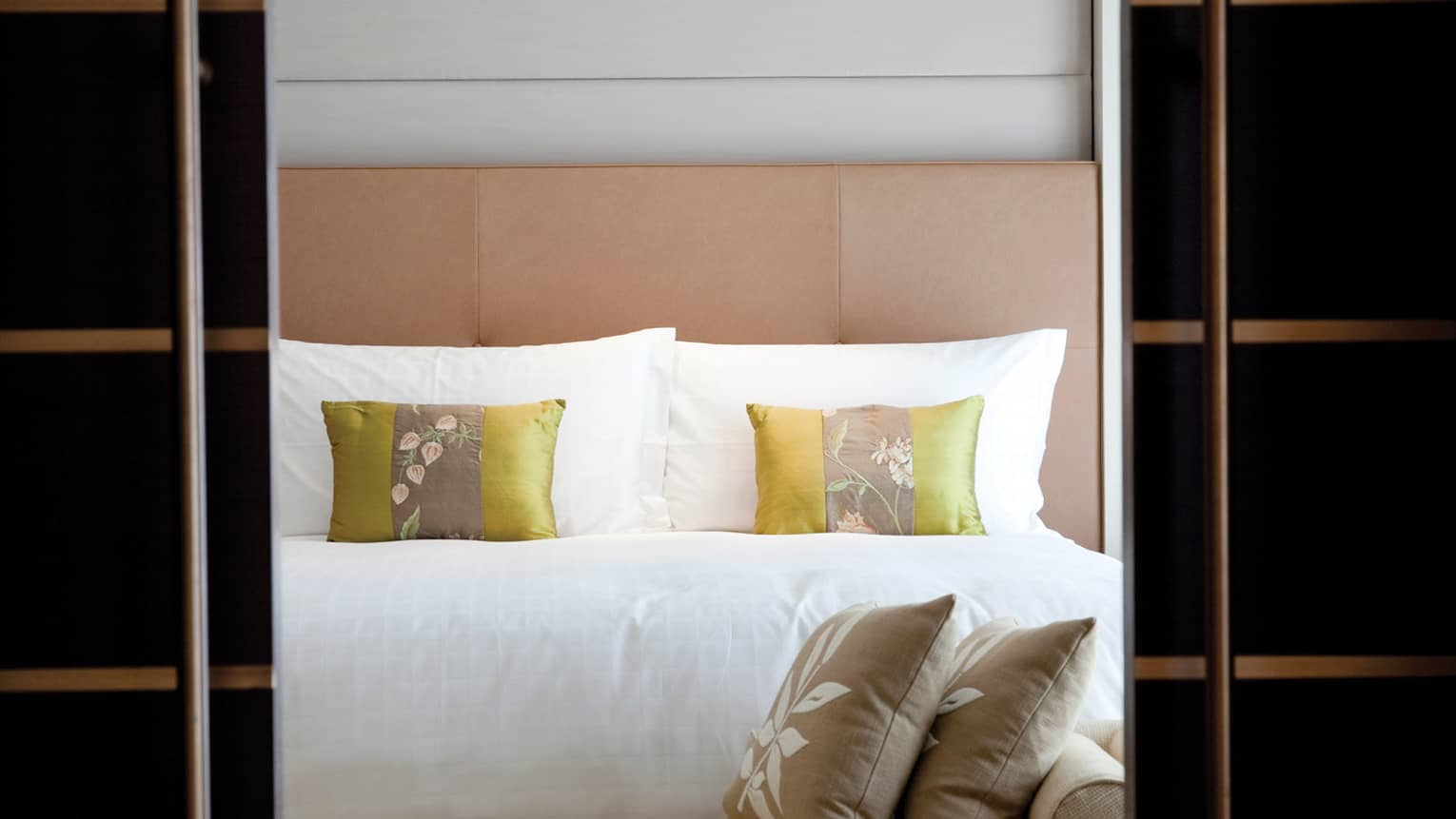 Close-up of hotel bed, padded headboard, small silk accent pillows