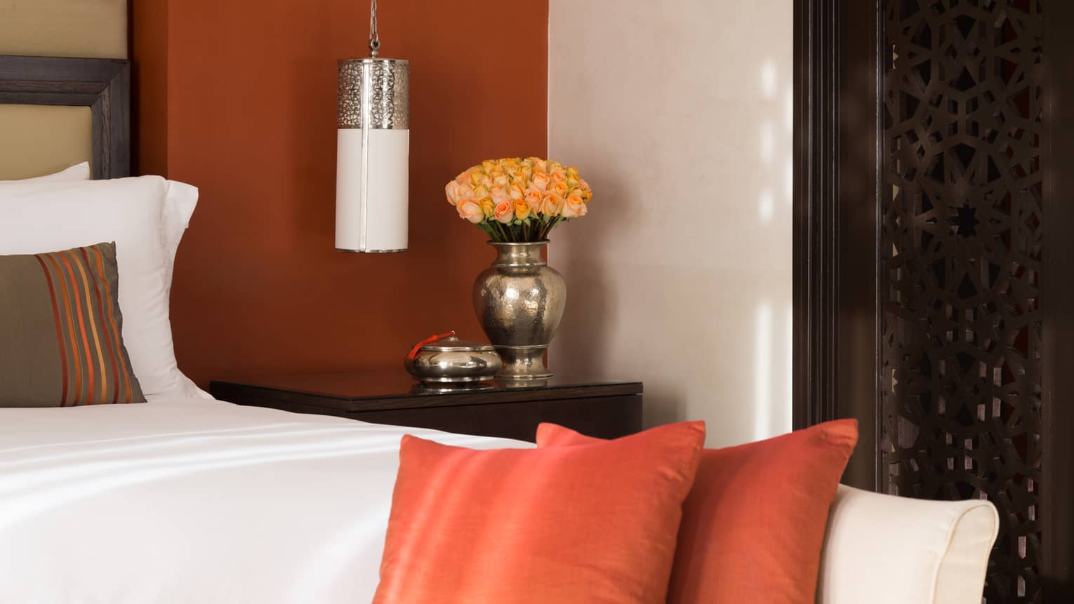 Close-up of hotel bed with orange and brown accent pillows, deep orange wall with white reading lamp