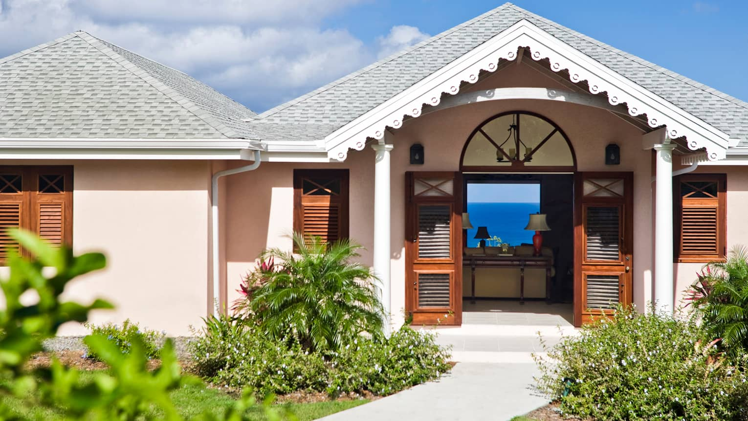 Sunset Hill Residence Villa exterior, pink bungalow with white trim