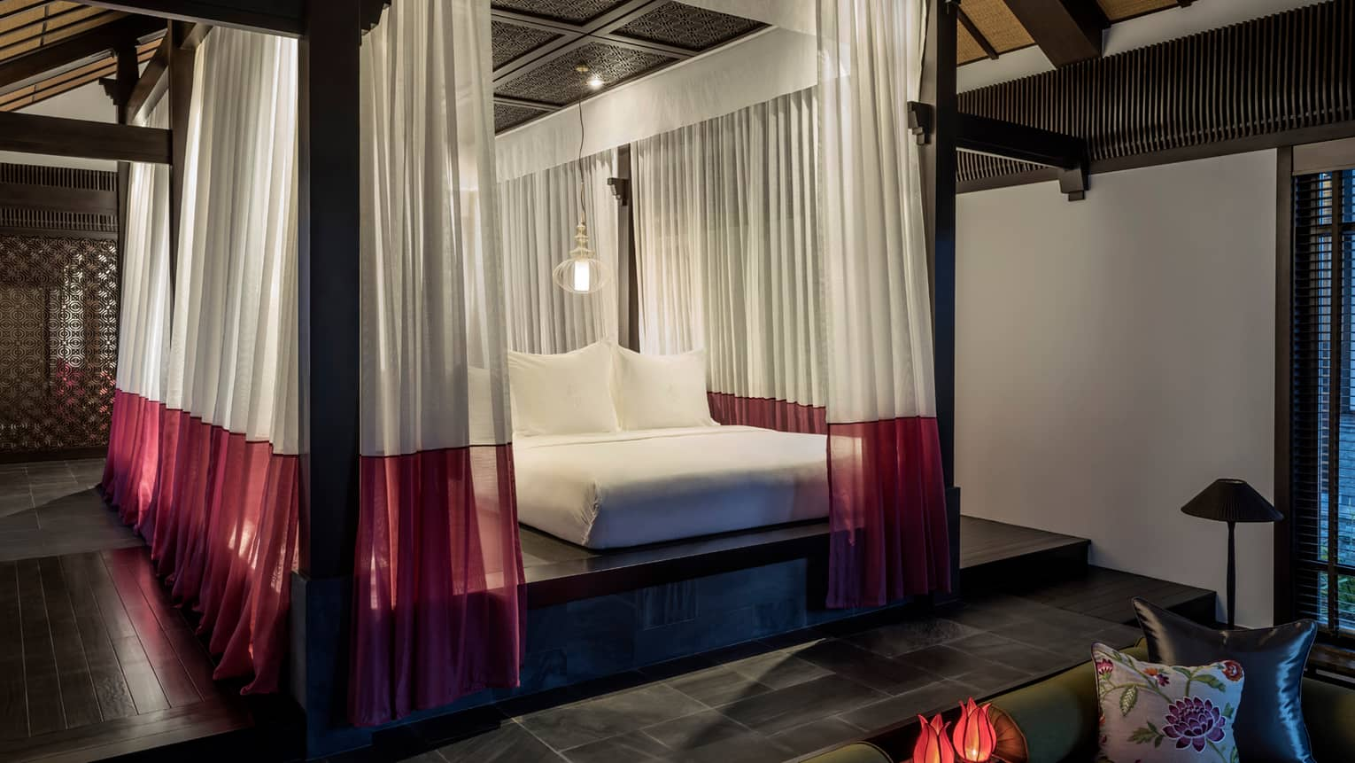 One-bedroom villa raised platform bed under sheer white-and-red drapes