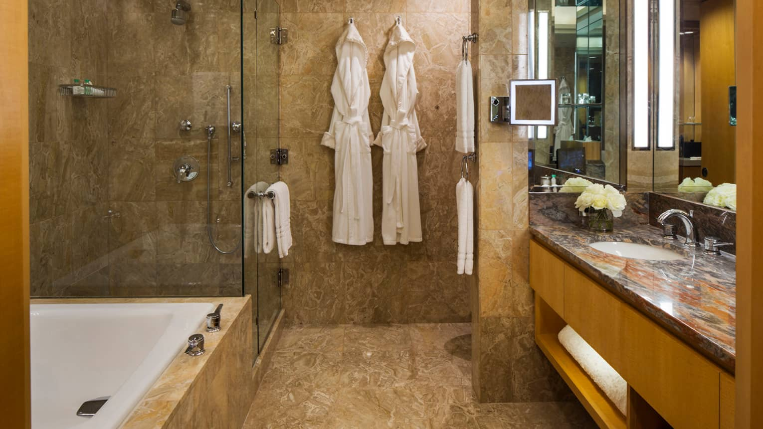 Gotham Suite bathroom, two white robes hanging on wall by walk-in glass shower, tub