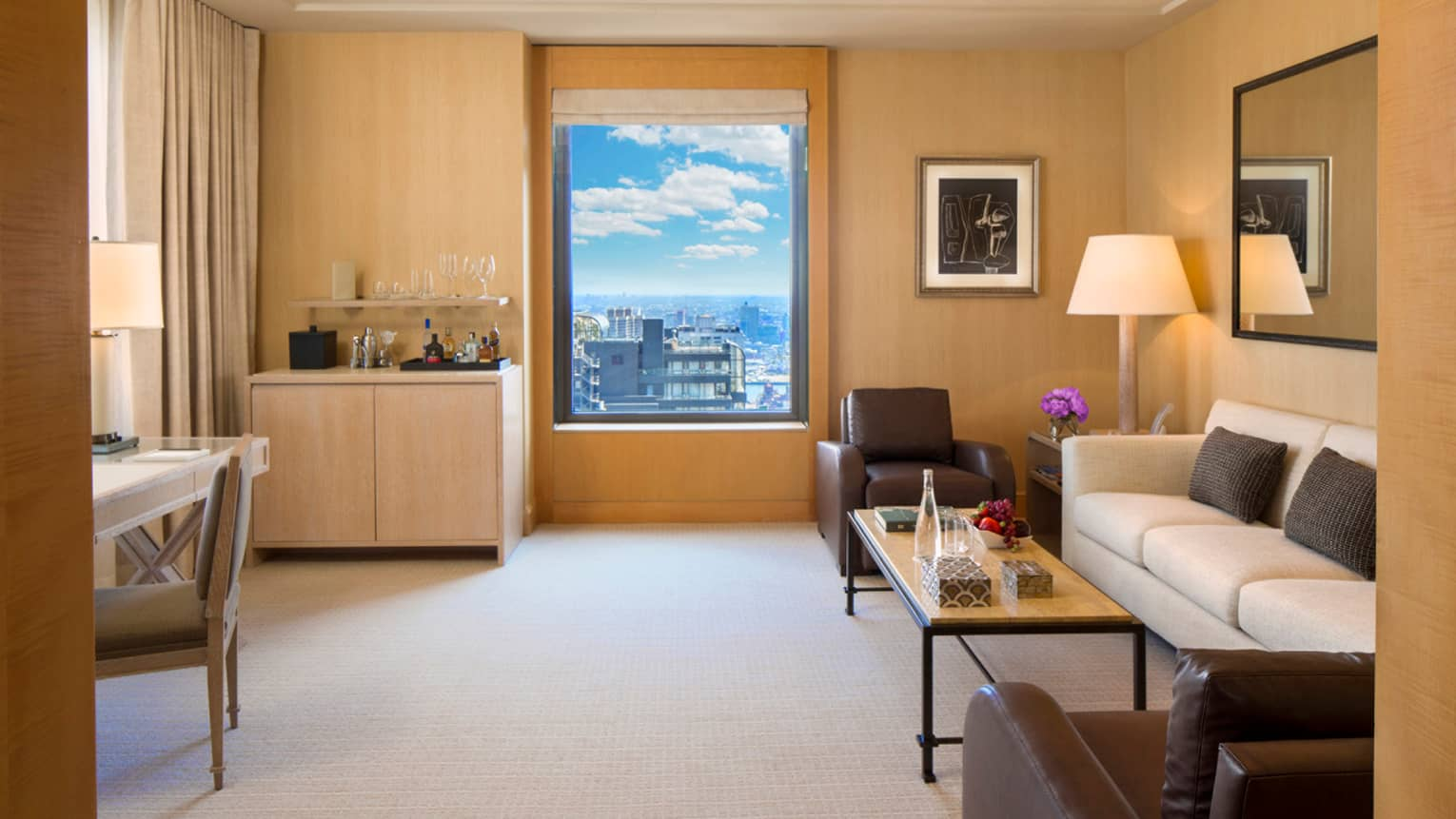 Park Avenue Suite small wet bar by window, white sofa with two brown leather chairs