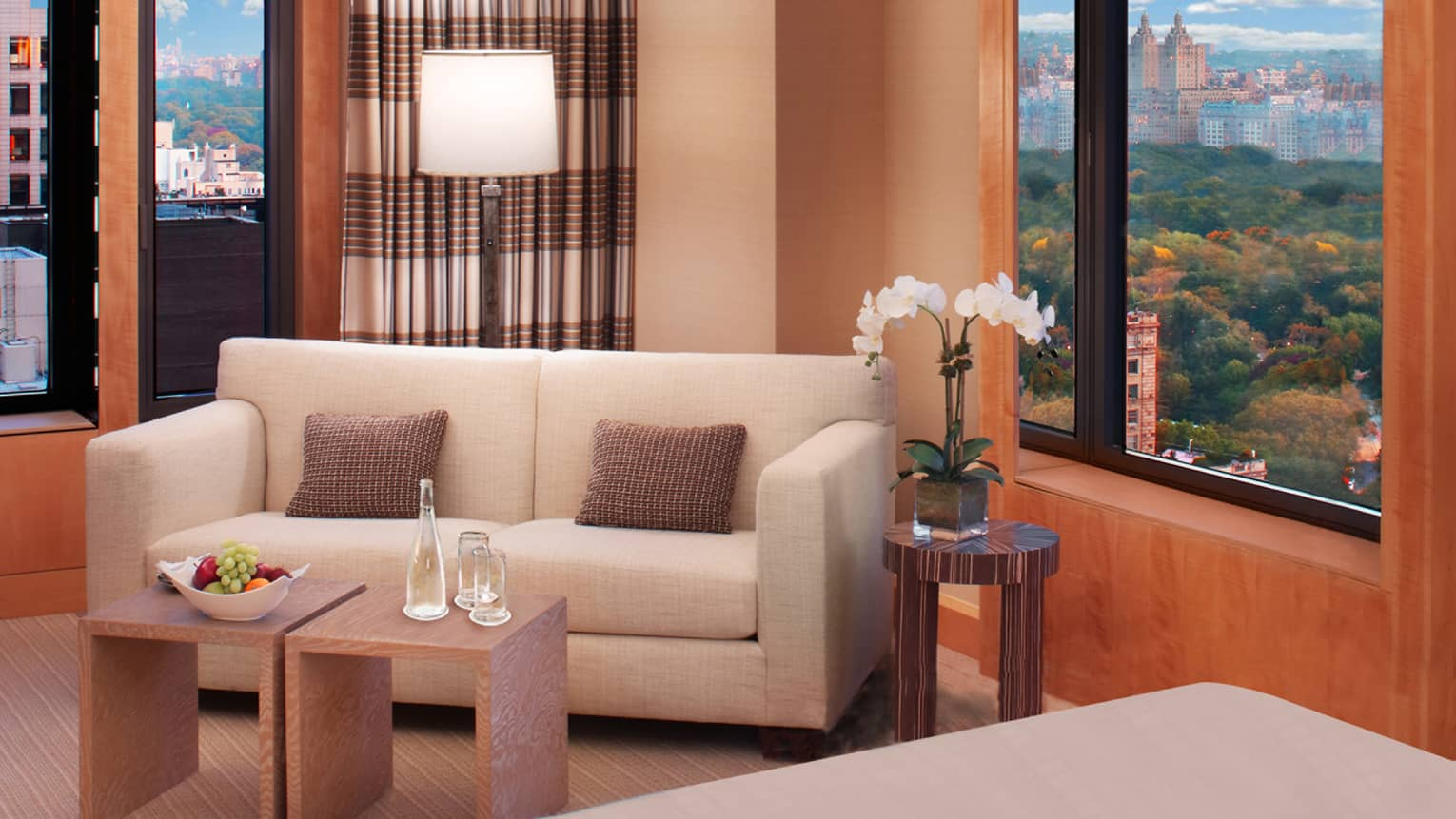 Corner suite with white loveseat sofa, small modern tables with fresh fruit, water, white orchid
