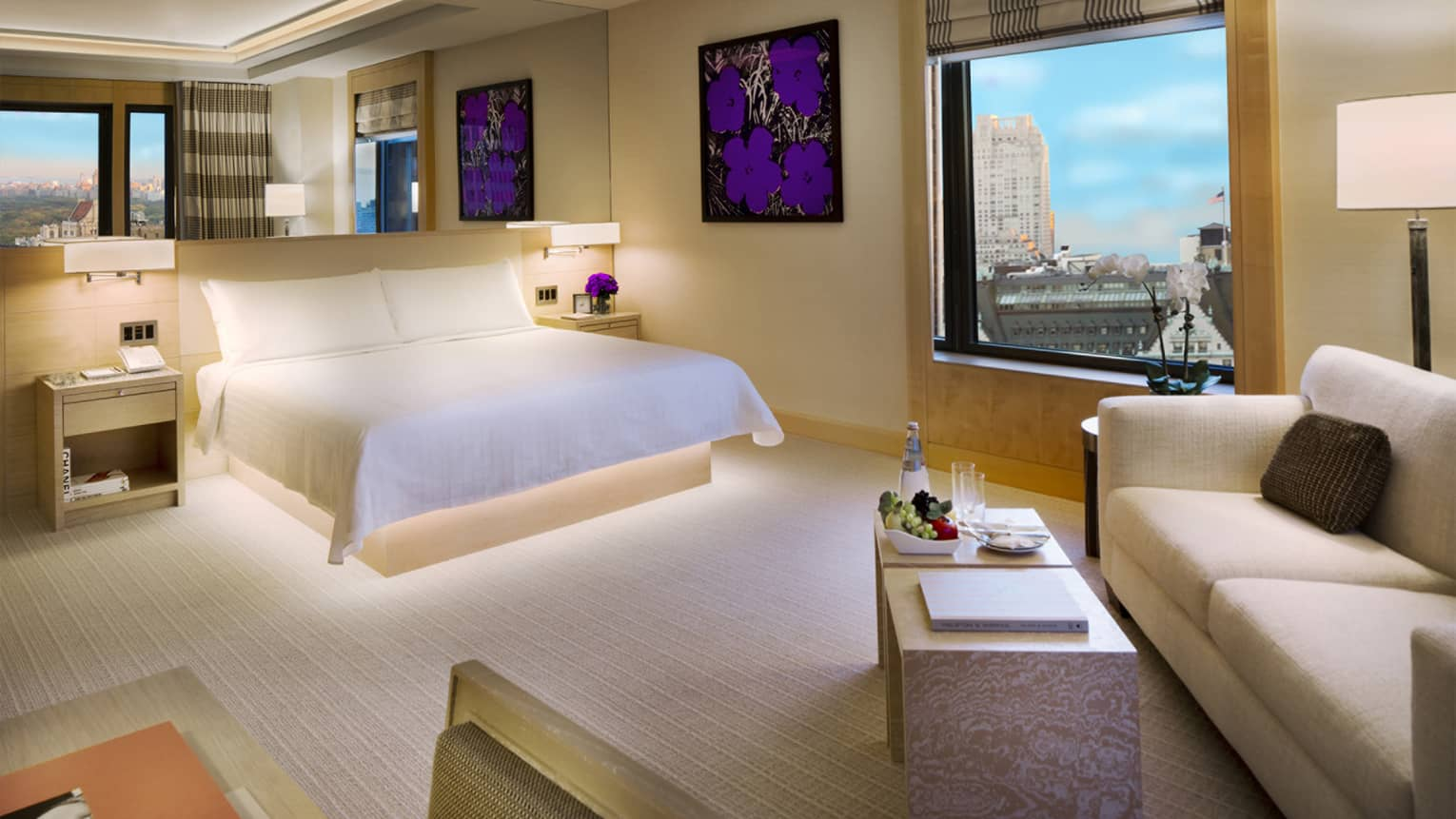 Modern Manhattan Junior Suite with framed purple flower print, white bed, sofa, window with park view