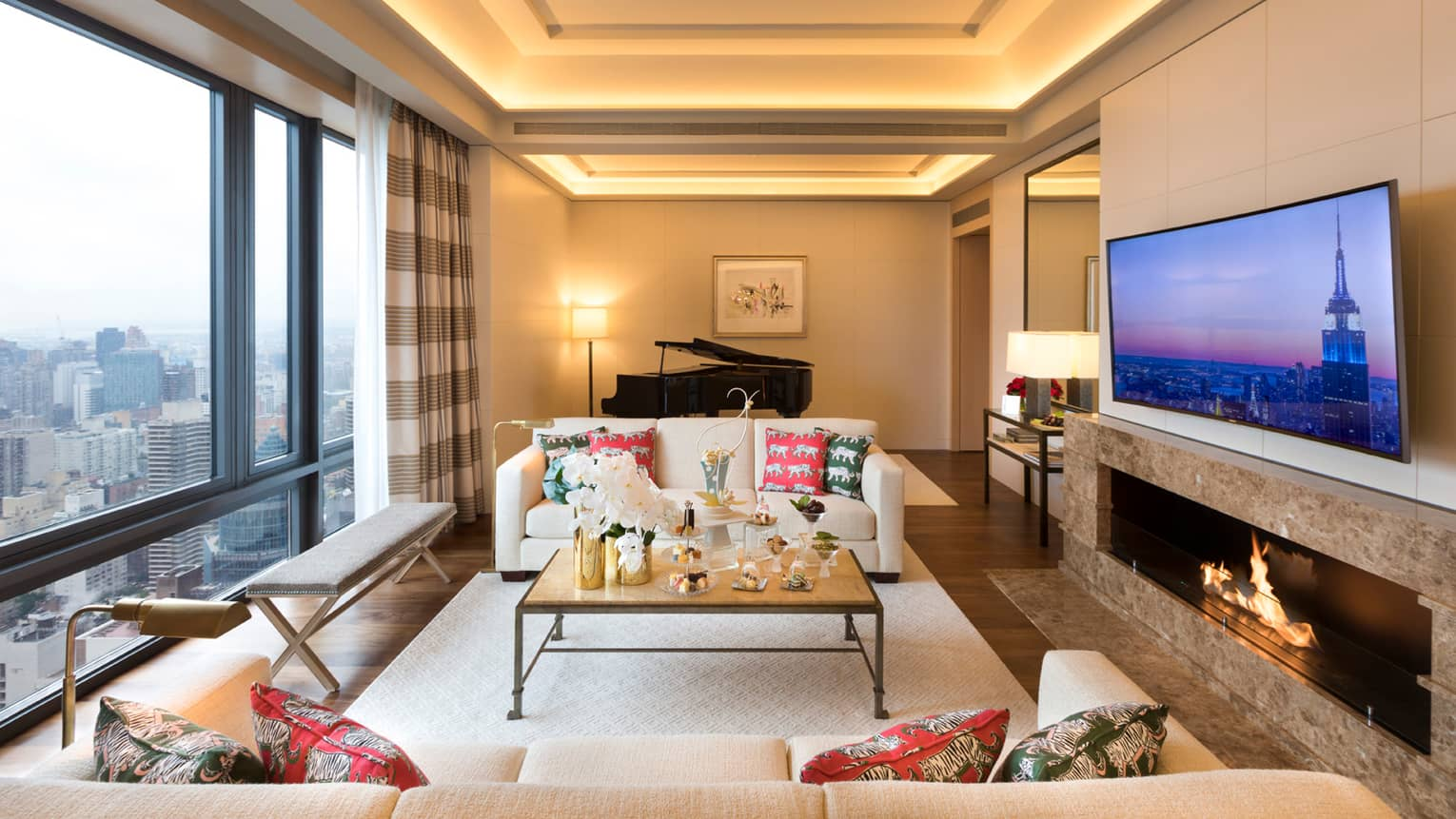 Gotham Suite sofas, tables with trays of sweets between floor-to-ceiling window, large TV