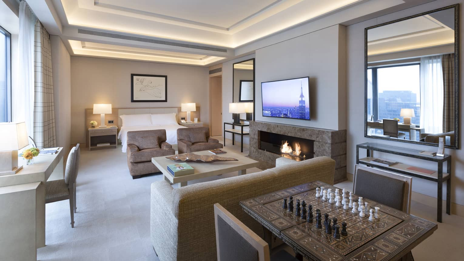 Gotham Suite table with chess board, seating area by fireplace and bed, desk at window