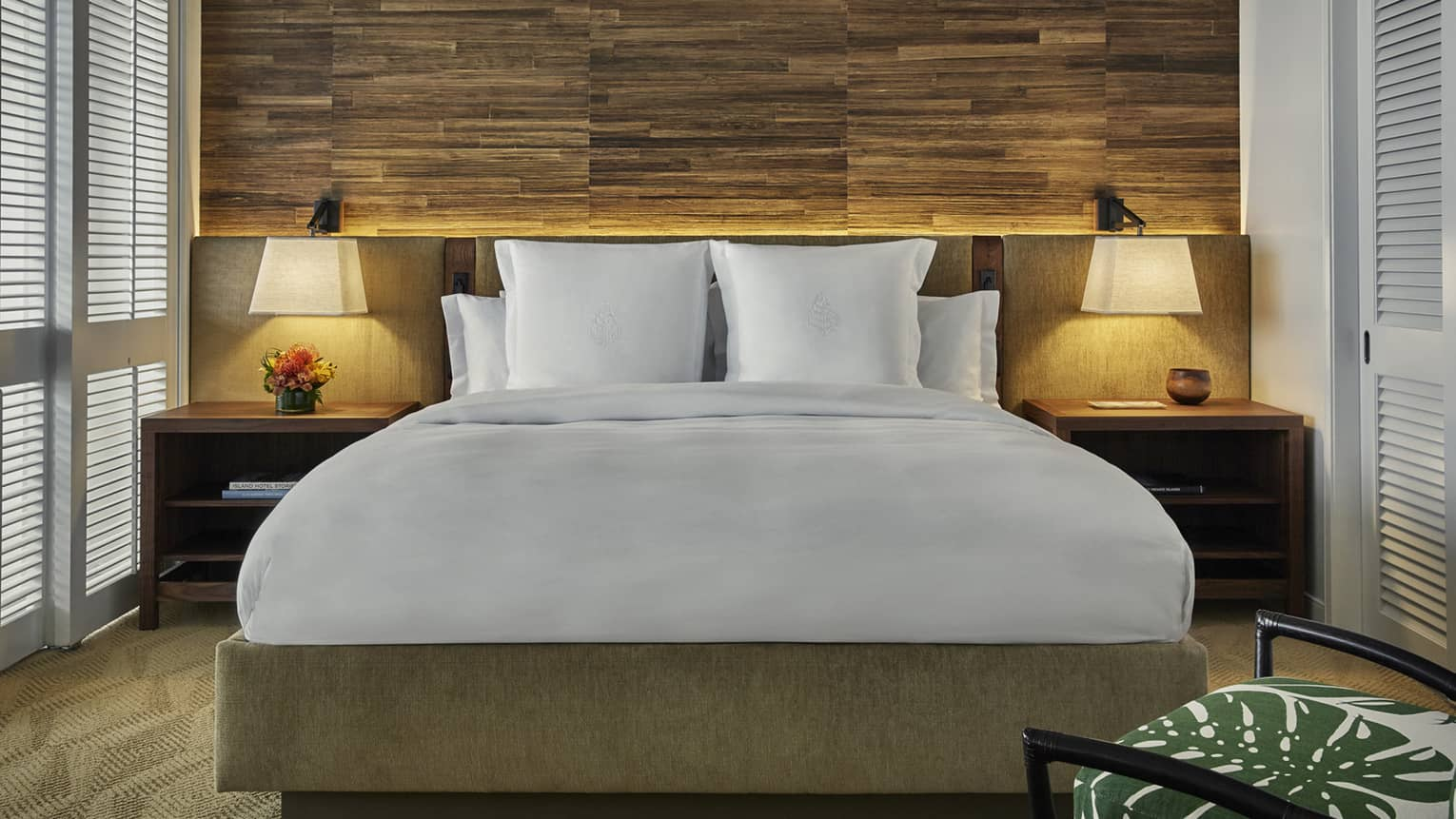 Bed with retro-style wood and upholstered headboard, nightstands, lamps, rustic wood wall