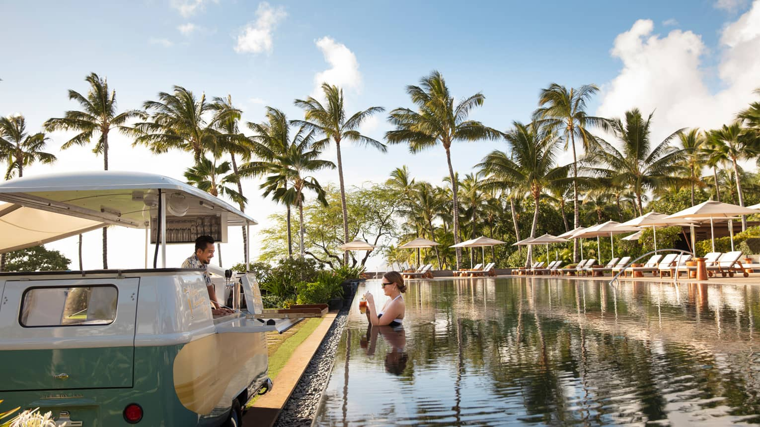 A woman orders a drink from Dr. Mai Tai's swim-up bar at the Four Seasons Resort Oahu infinity pool