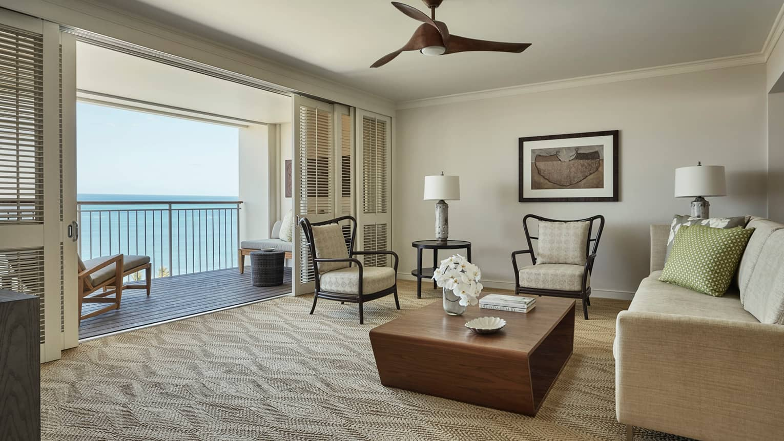 Oceanfront Suite chairs, wood table, sofa facing open wall, sliding shutters, balcony