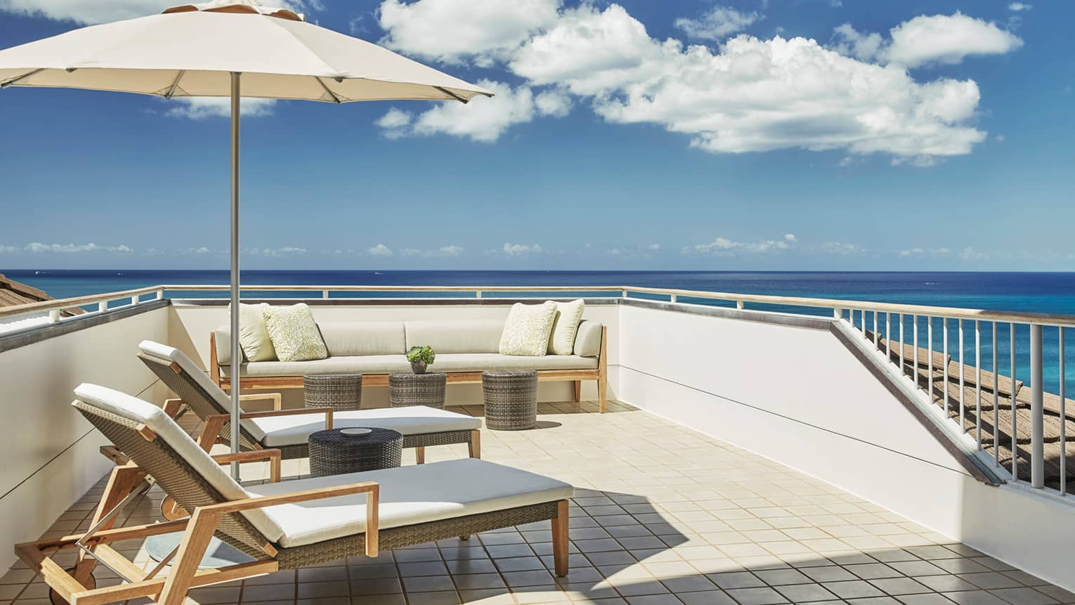 White cushioned wicker patio furniture, umbrella on rooftop balcony