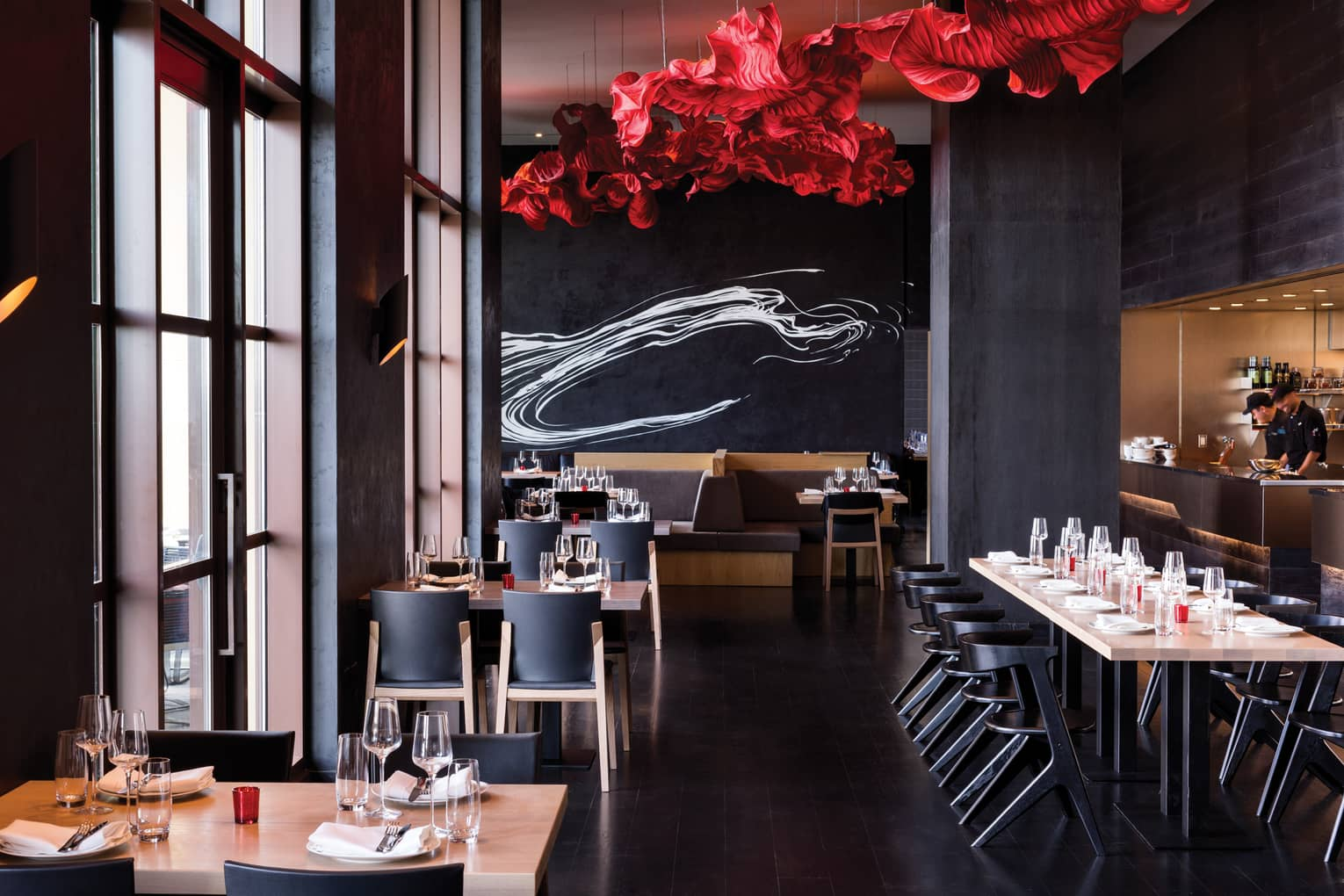 A red sculpture on the ceiling and red and white accents illuminate the Capa dining room