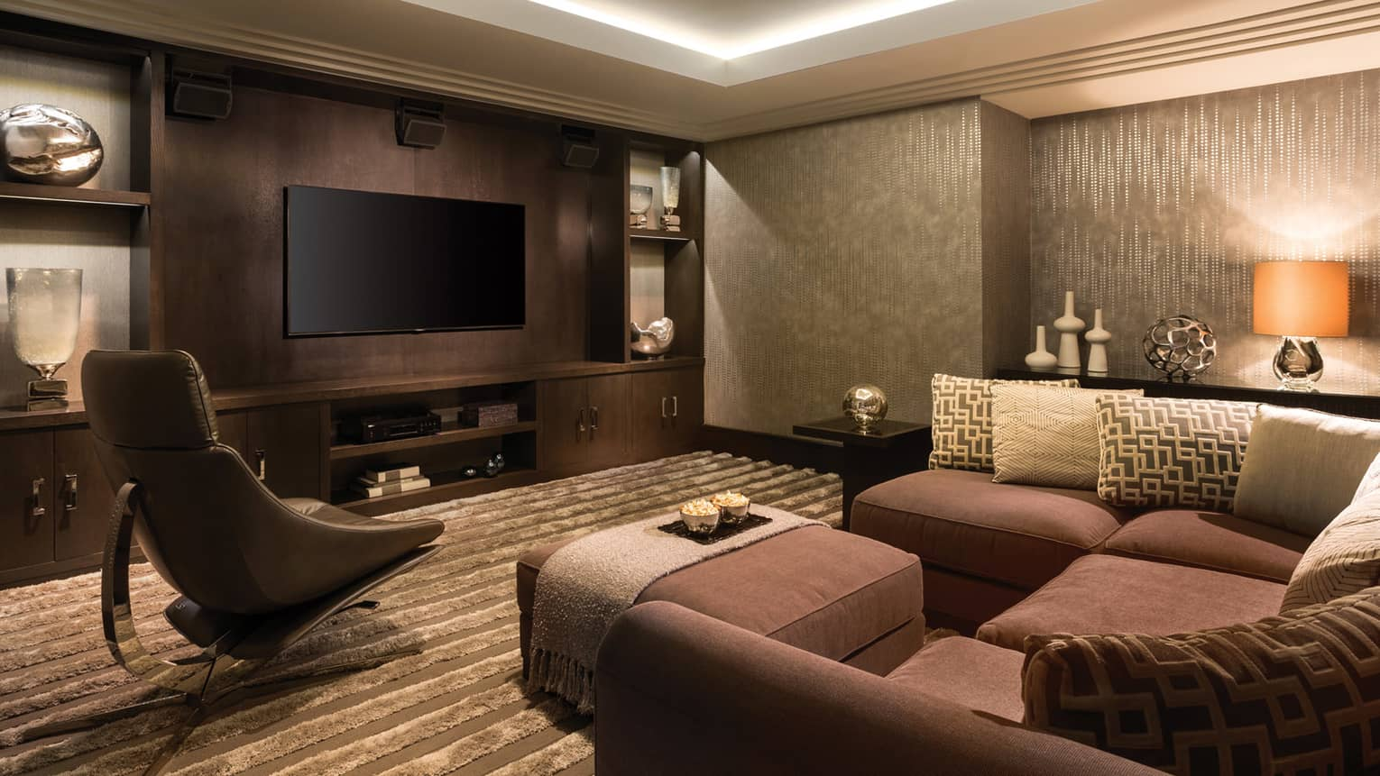 TV on wood panel wall. cabinet, across from L-shaped brown sofa, plush ottoman, modern leather chair
