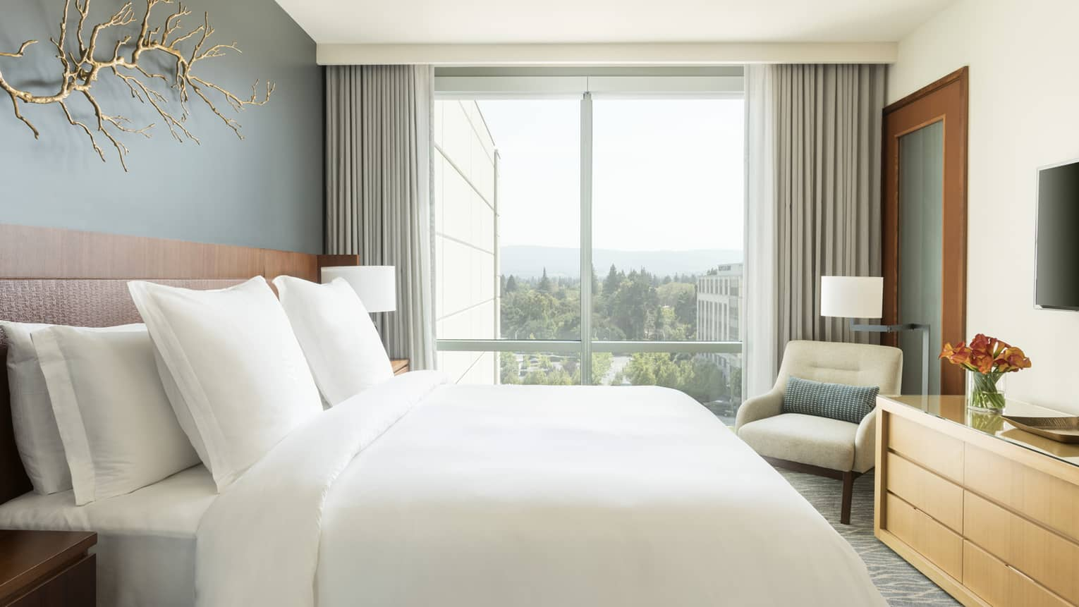 Modern, bright hotel room with gold branch on wall above bed, floor-to-ceiling window
