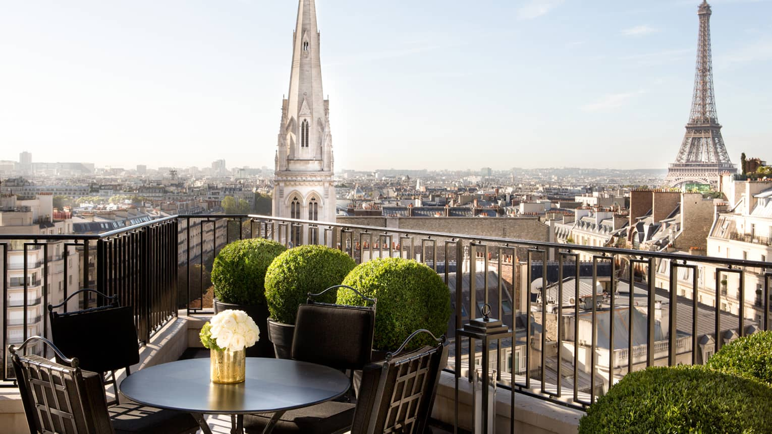 Patio dining table with white roses, potted shrubs iron balcony overlooking Paris rooftops, cathedrals