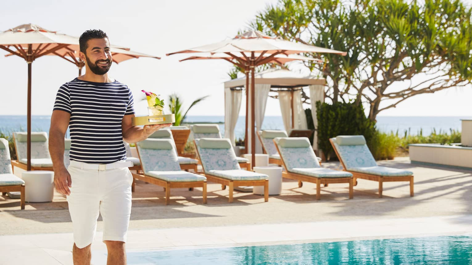 Staff member in blue striped shirt, white bermuda shorts, carrying drink tray, outdoor poolside