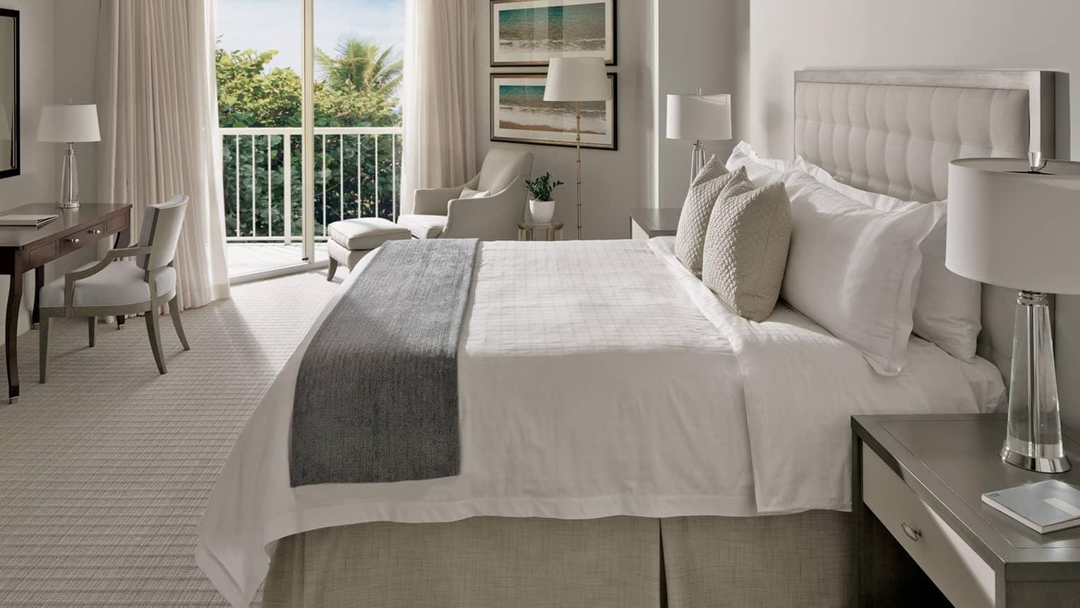 Garden-View Room bed with ivory pillows, grey bedspread, office desk and balcony