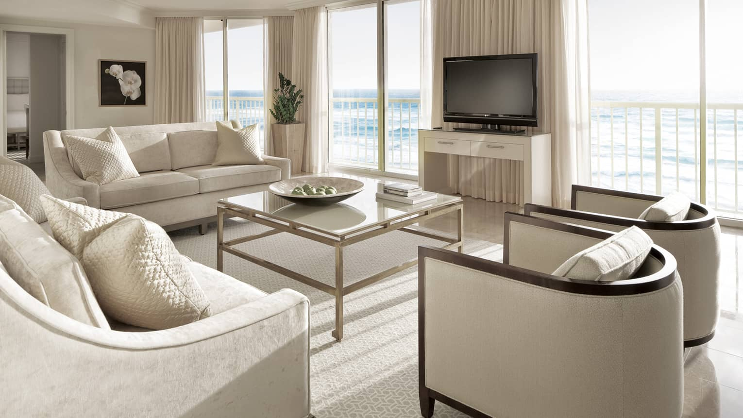 Deluxe Oceanfront Suite with white sofas and armchairs, glass coffee table, juliet balcony, ocean view