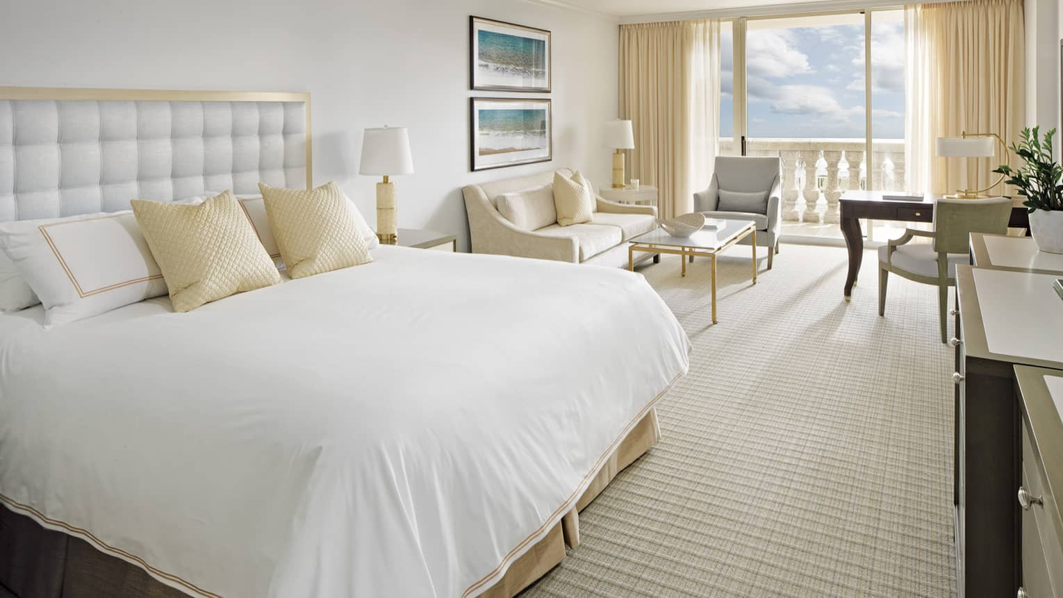 Premier Ocean View Suite bed with white padded headboard, gold pillows, living area and white pillar balcony