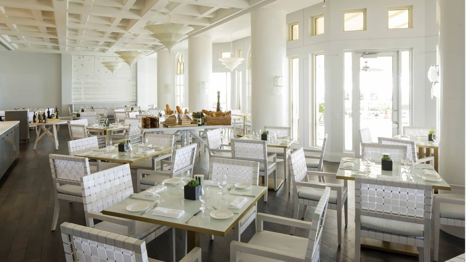 Graze dining room with white columns, tables and white picnic-style chairs, table with bread baskets and olive oil