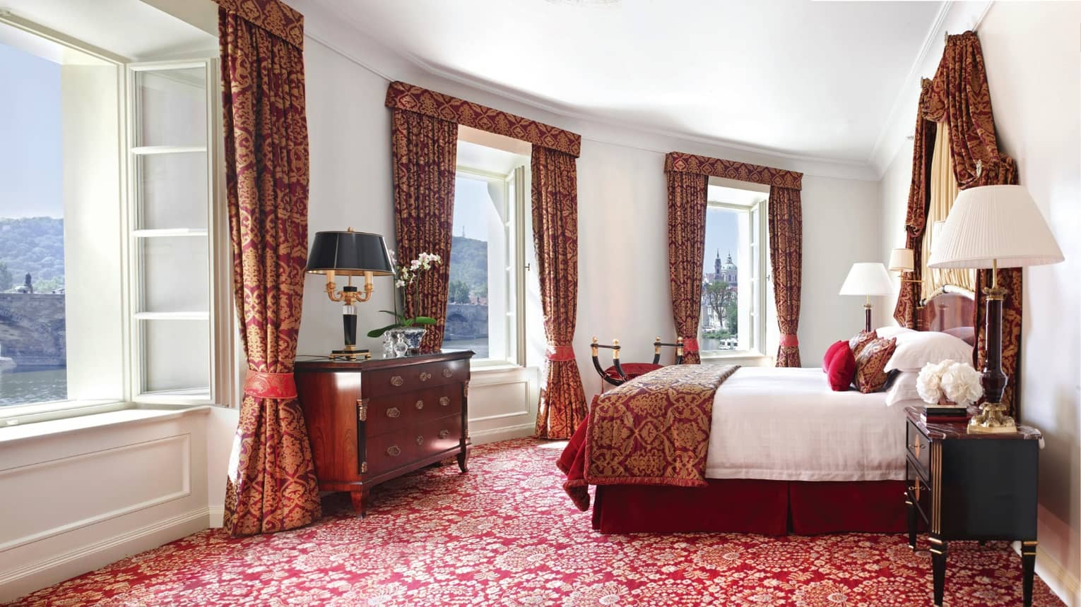 Presidential Suite with bright windows along curved wall, Baroque-inspired red-and-gold carpet, curtains
