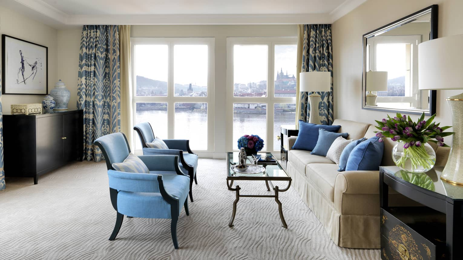 River Suite with two blue armchairs in front of glass coffee table, sofa, floor-to-ceiling windows with Vltava River view