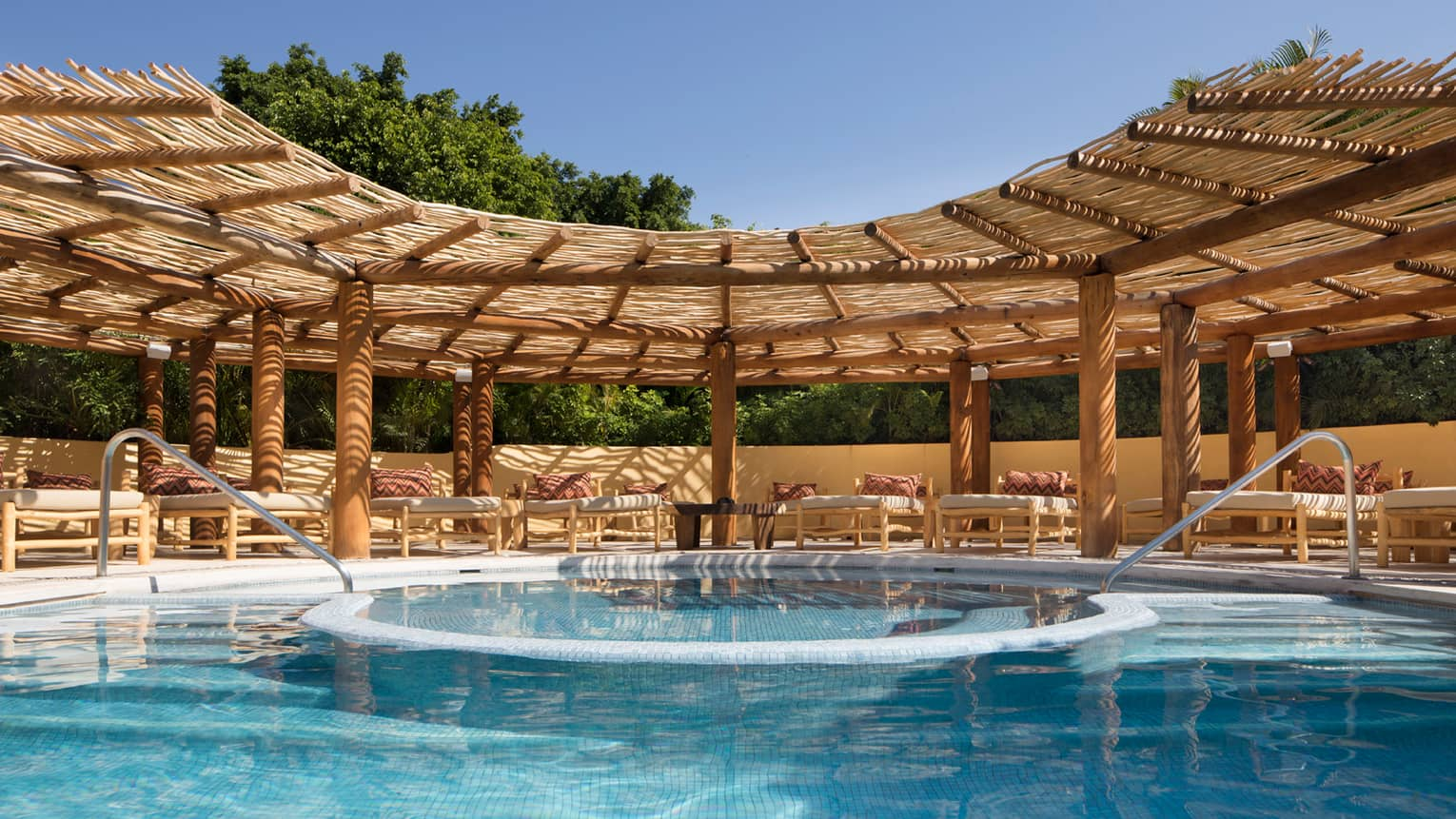 Curved trellis over Tamai Pool Complex blue swimming pool, flat white lounge chairs