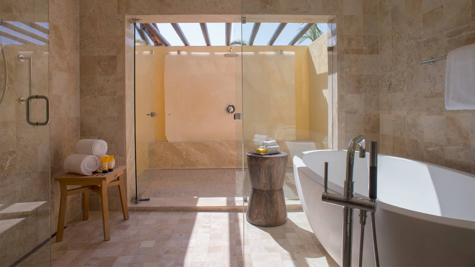 Large outdoor walk-in shower with pink tiles, glass doors, rolled white towels on table
