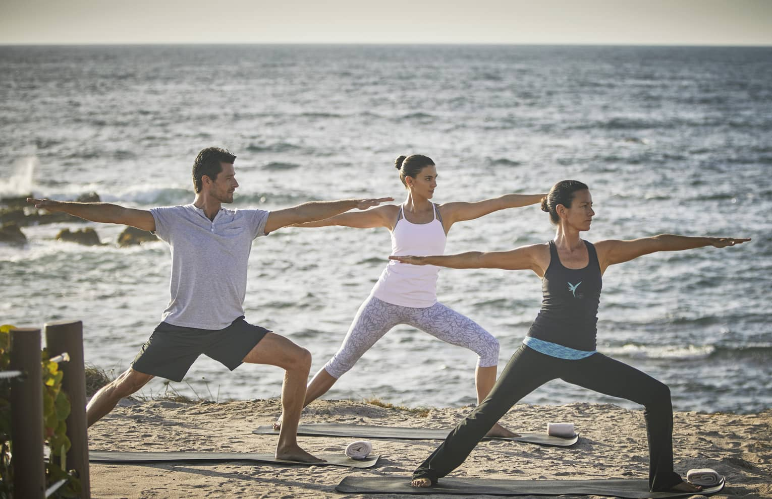 Three people with arms outstretched in yoga pose on beach